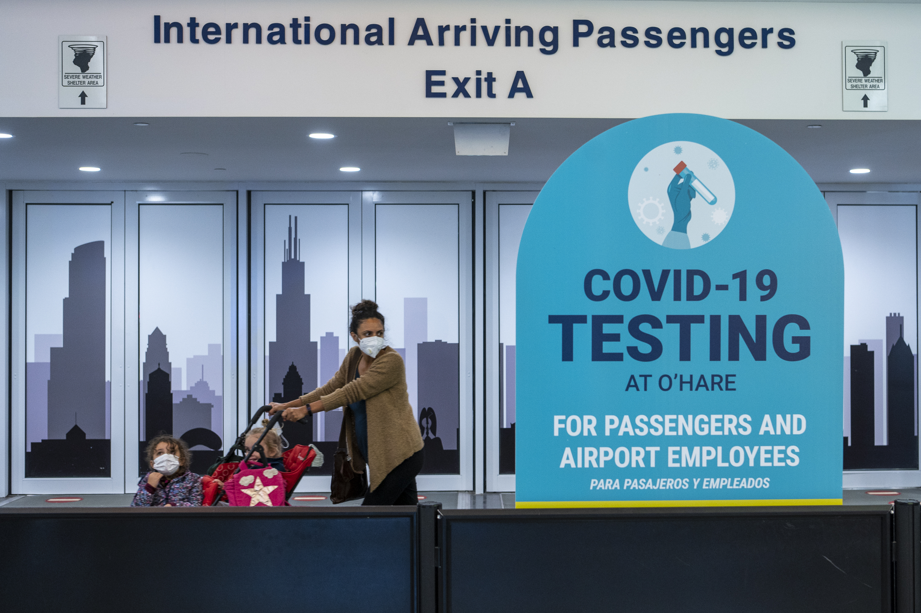 A woman pushes a stroller with children after exiting the security screening at O'Hare International Airport's International Terminal last week. No travel quarantine restrictions are in place for people arriving to Chicago from any U.S. state.