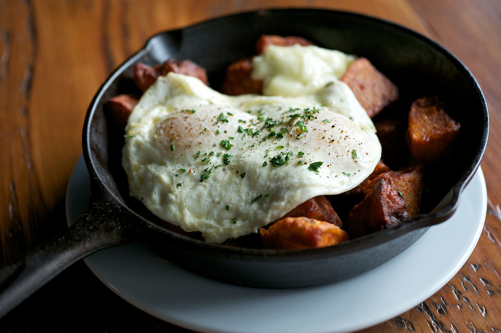 Tasty N Sons potatoes come in a small cast-iron pan with a fried egg draped over top.