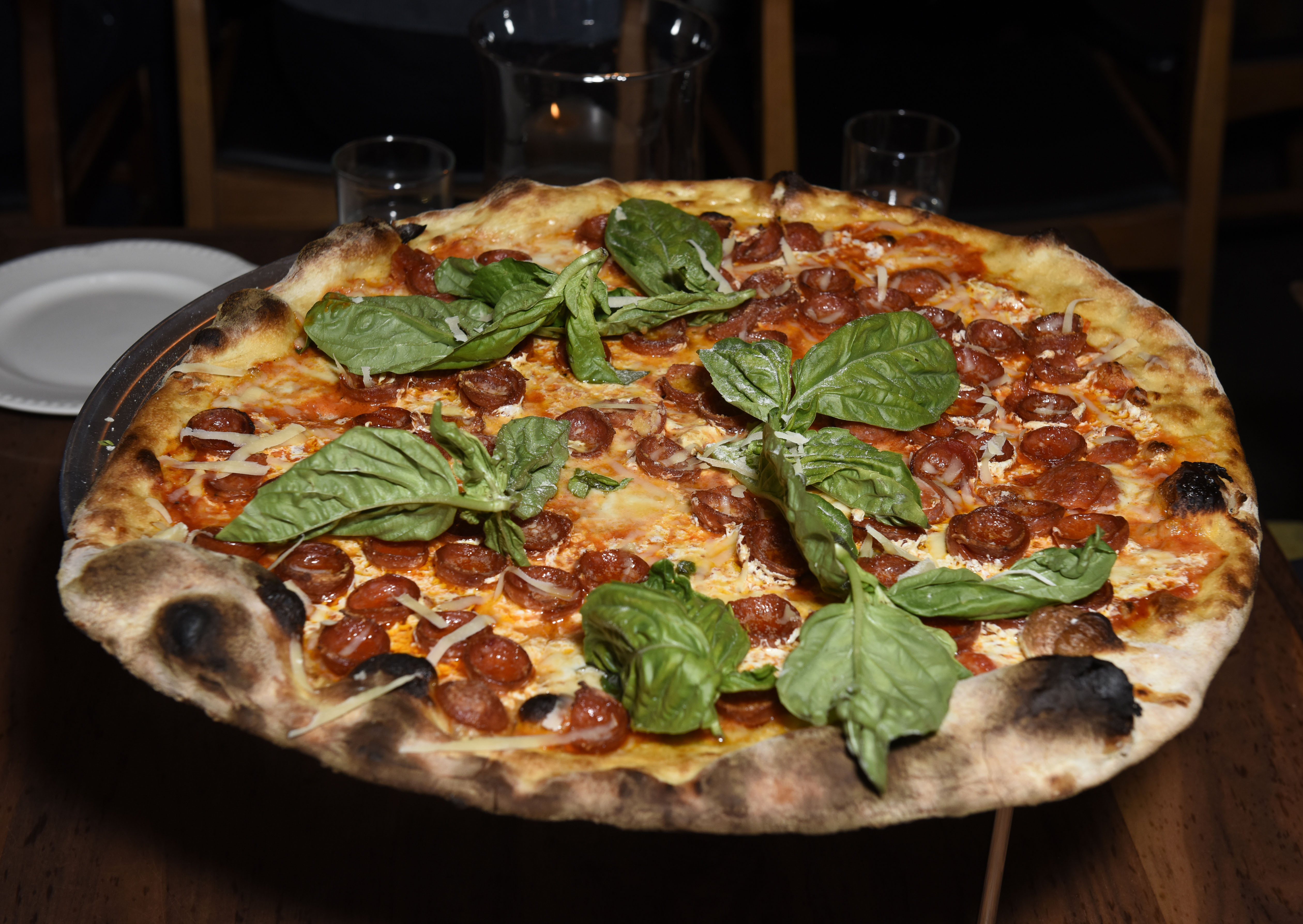 A pepperoni pie with green basil leaves strewn across the top