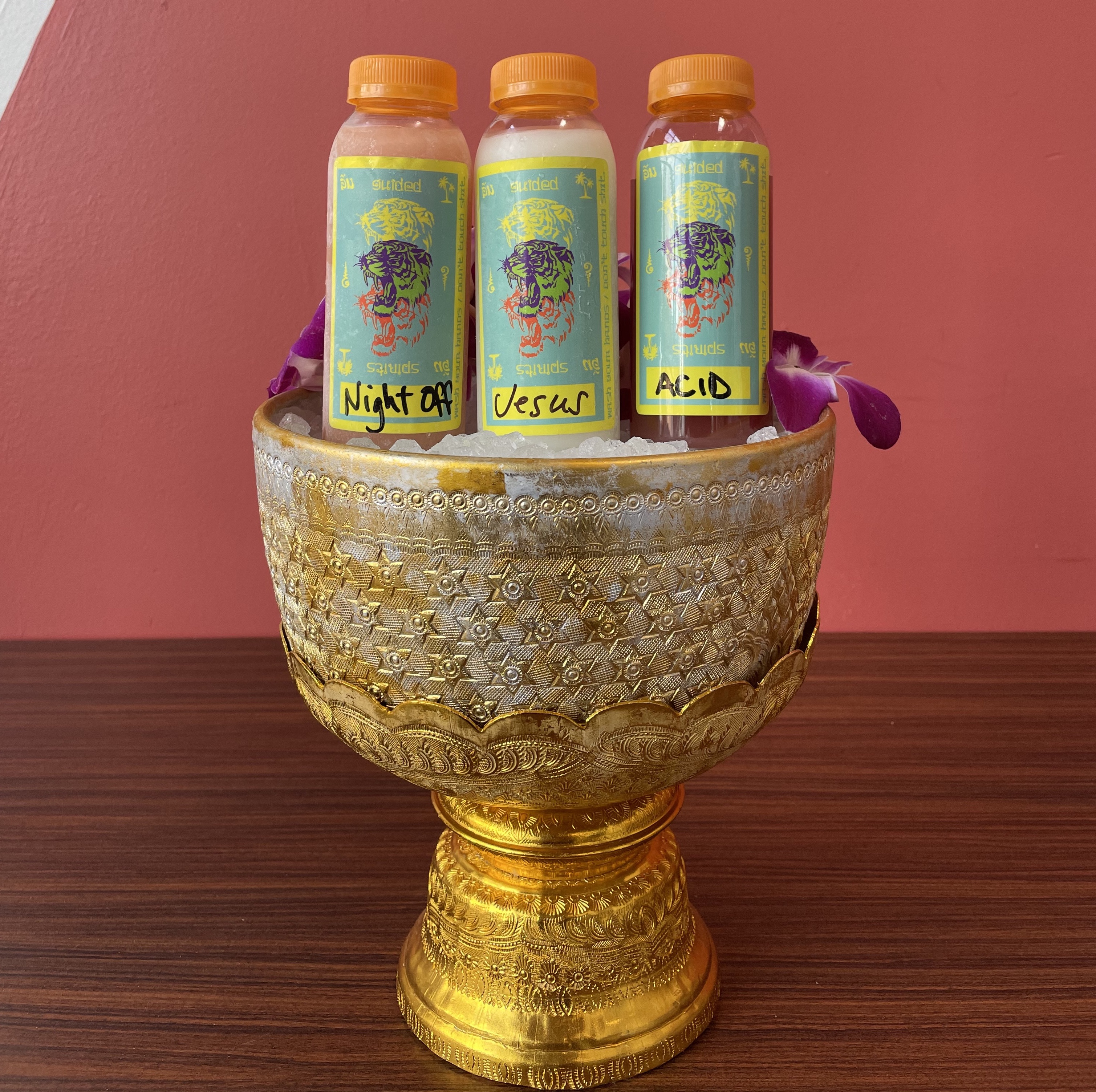 A gold bold on a wooden platform holds three bottled cocktails with labels from Eem