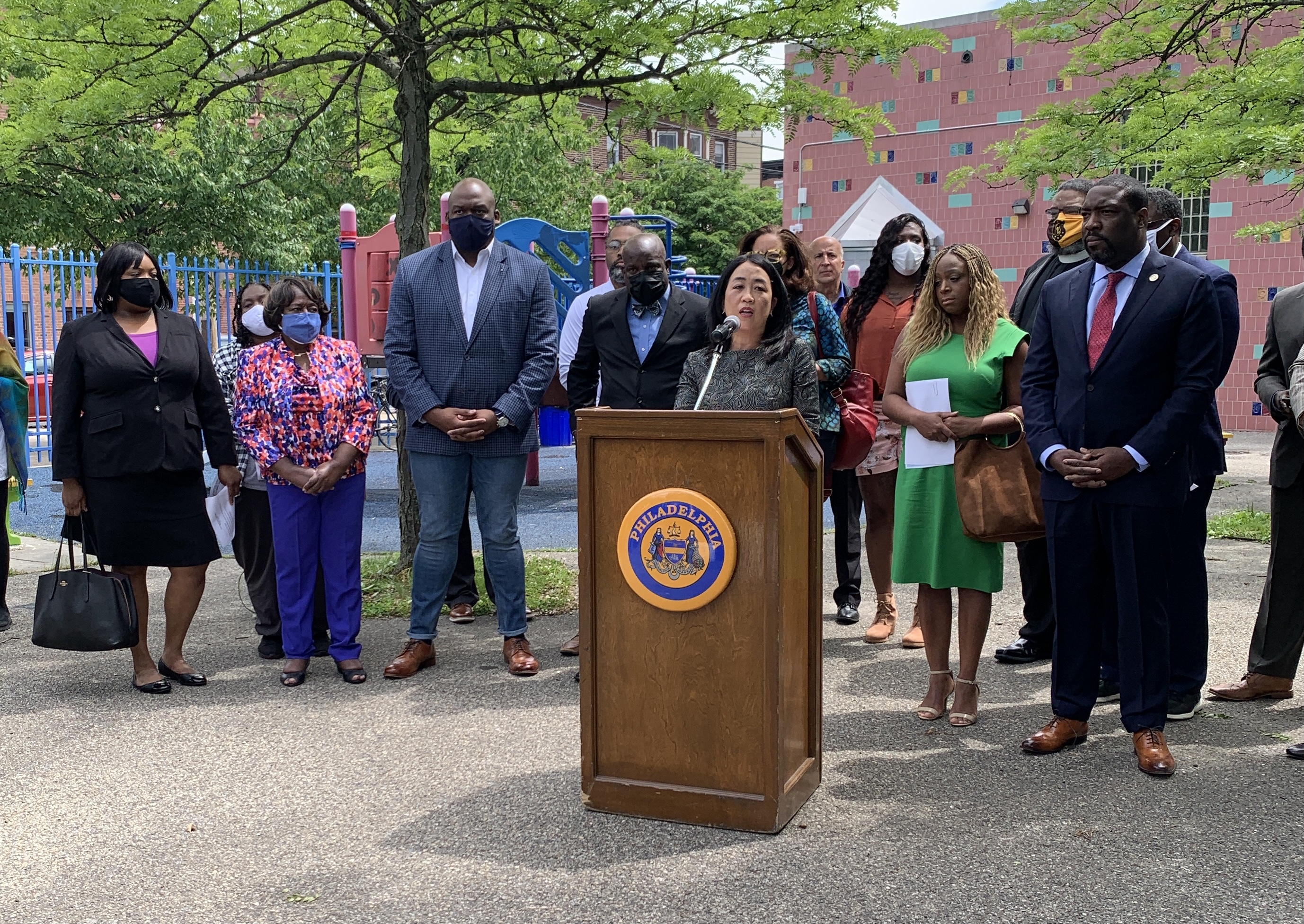 Council member Helen Gym is standing at a lectern outside and is surroundedby several other council members, community and religious leaders.