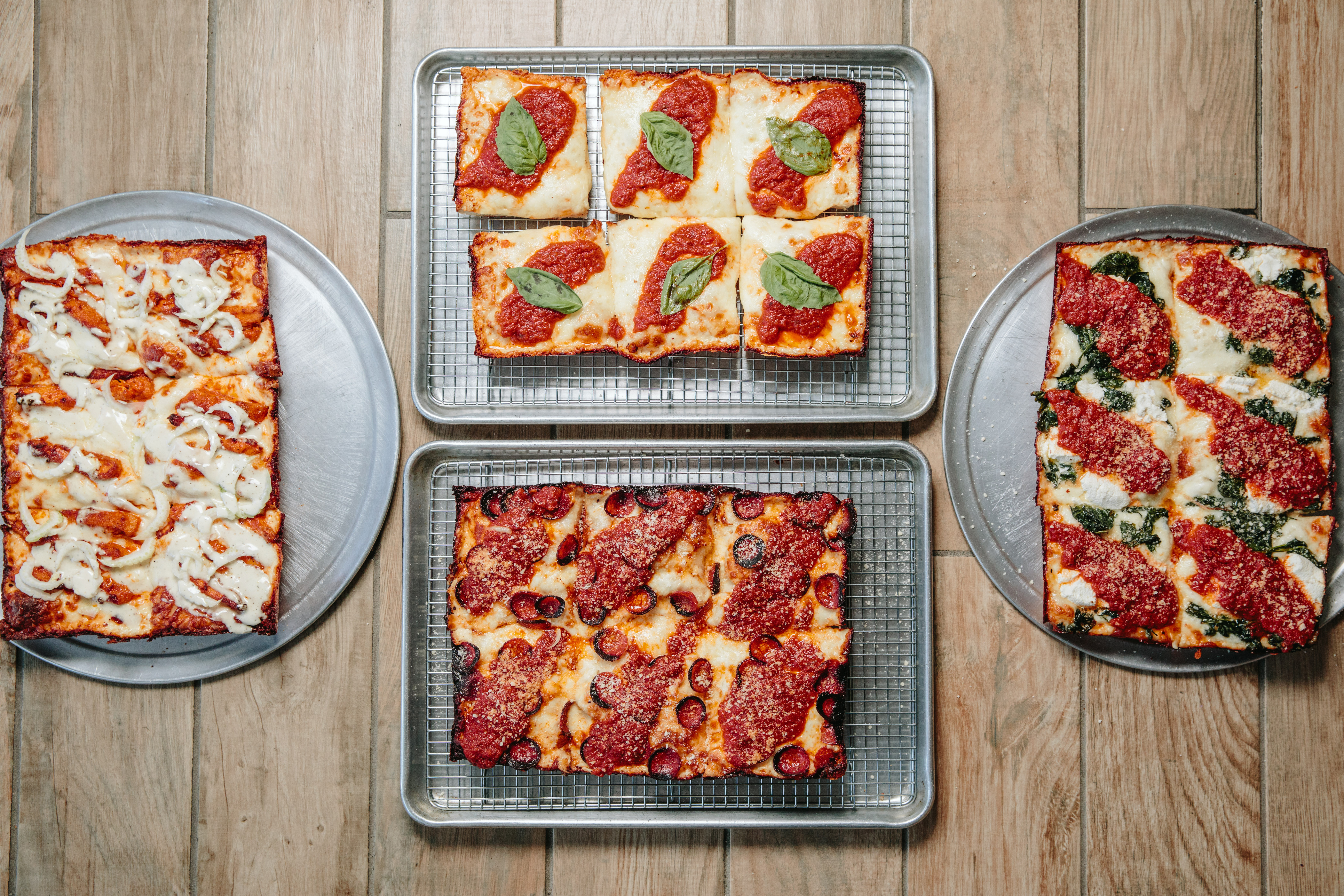 Overhead view of four rectangular Detroit-style pizzas on steel pans on a wooden table