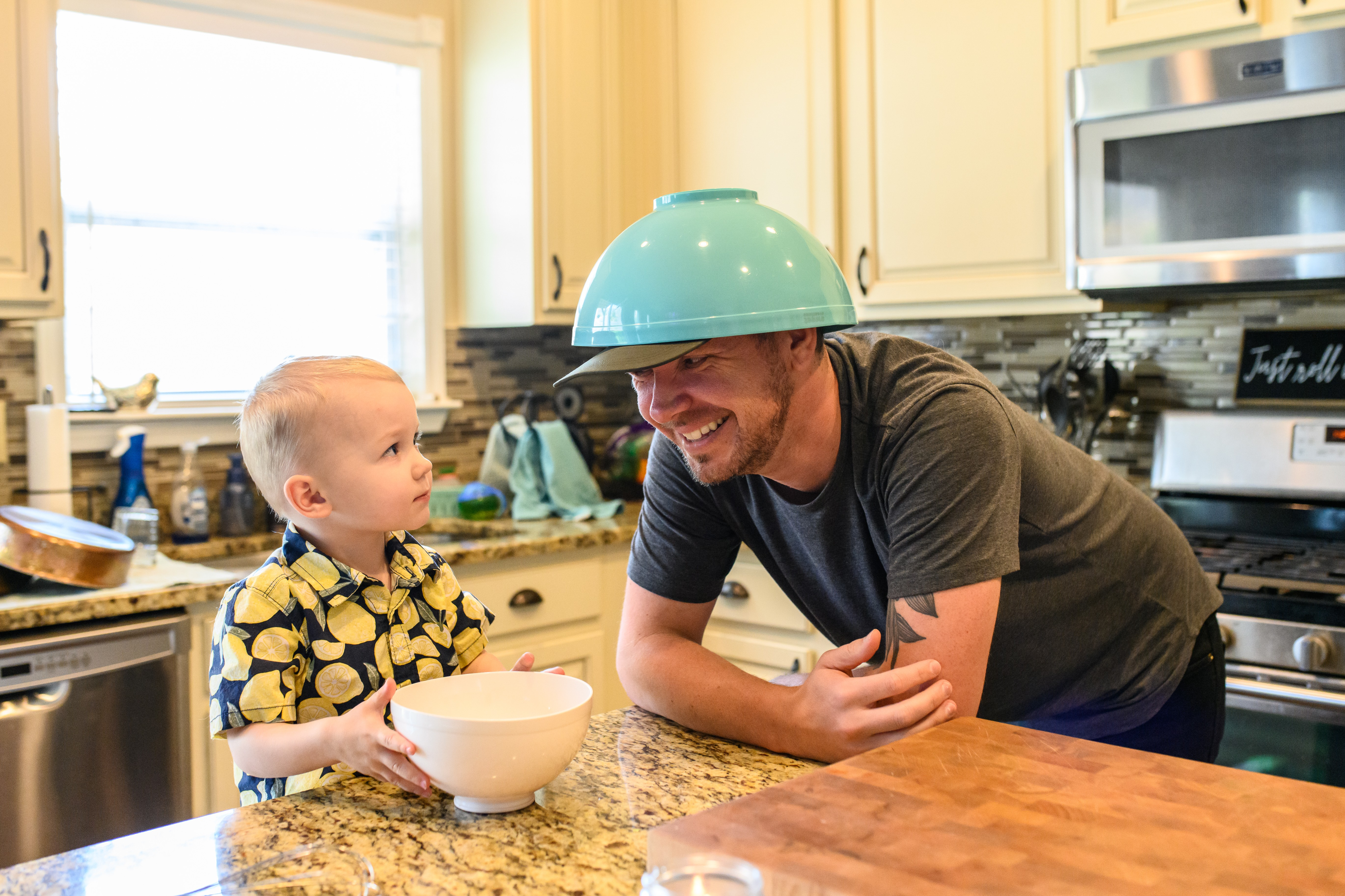 Beaming man leans over a kitchen counter with a bowl on atop of his head; he's smiling at a toddler who's looking up at him.