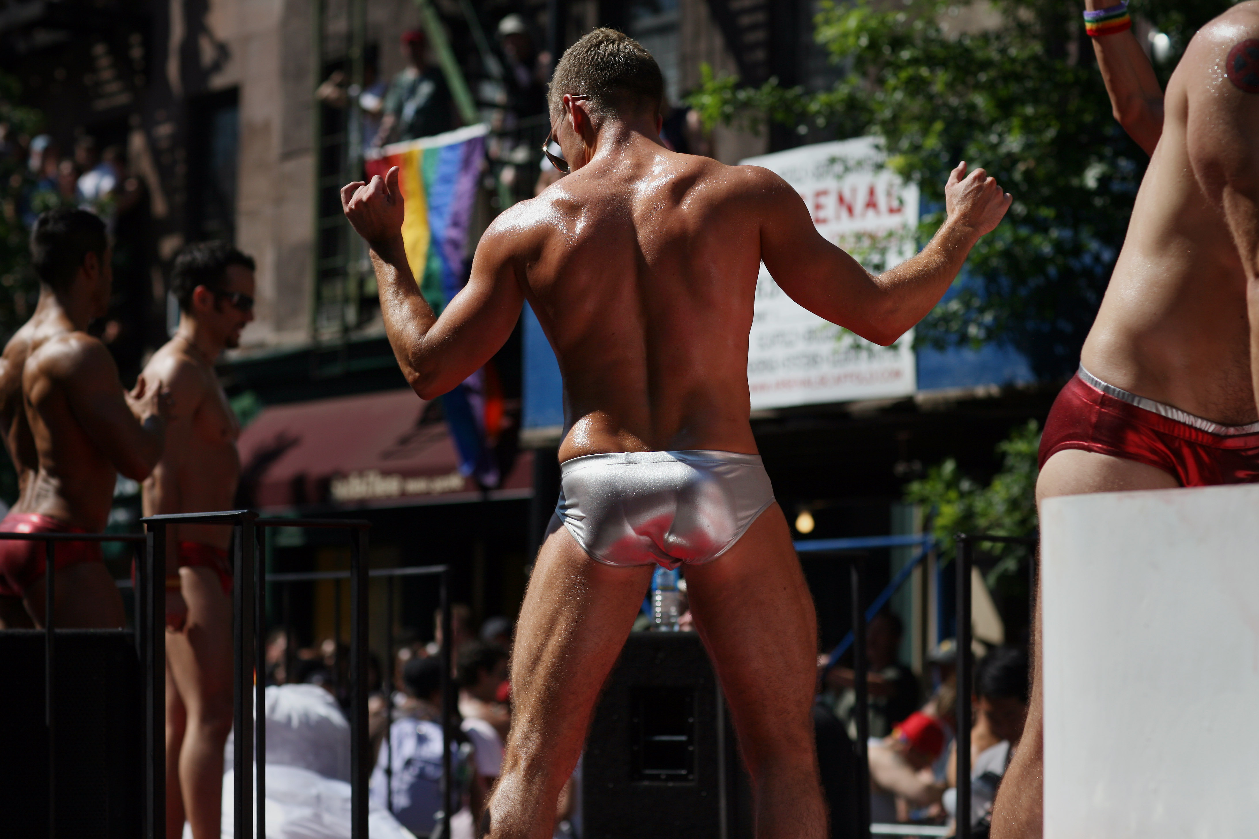 A man in the New York Pride Parade wearing shiny silver briefs and nothing else.