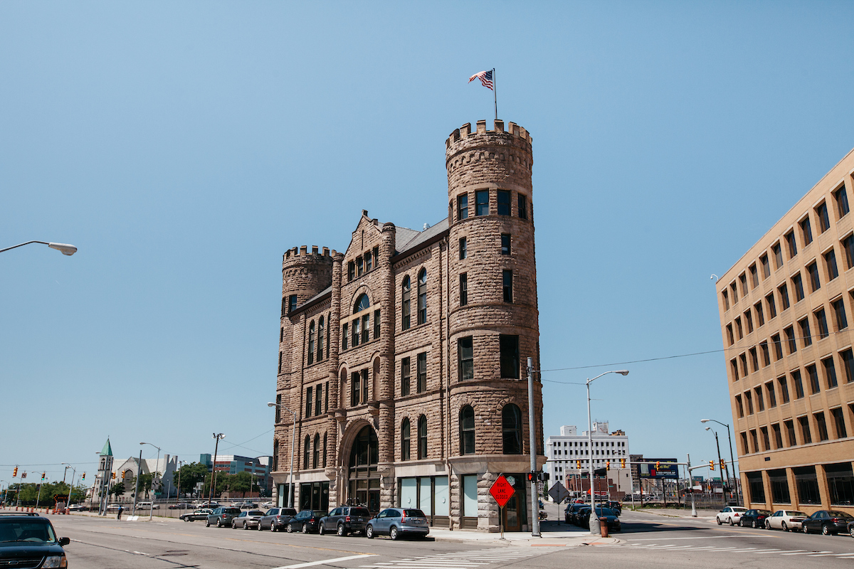 A five-story castle-like structure sits at the intersection of three cross streets