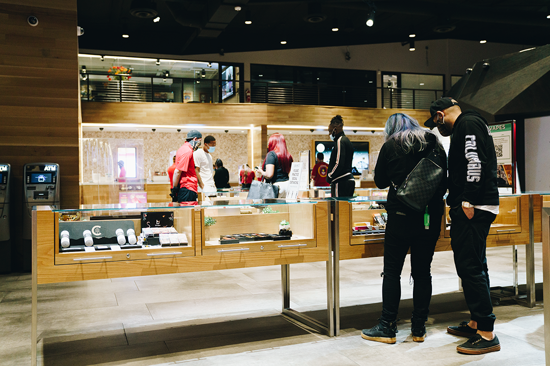 Two people shop at a case in a store