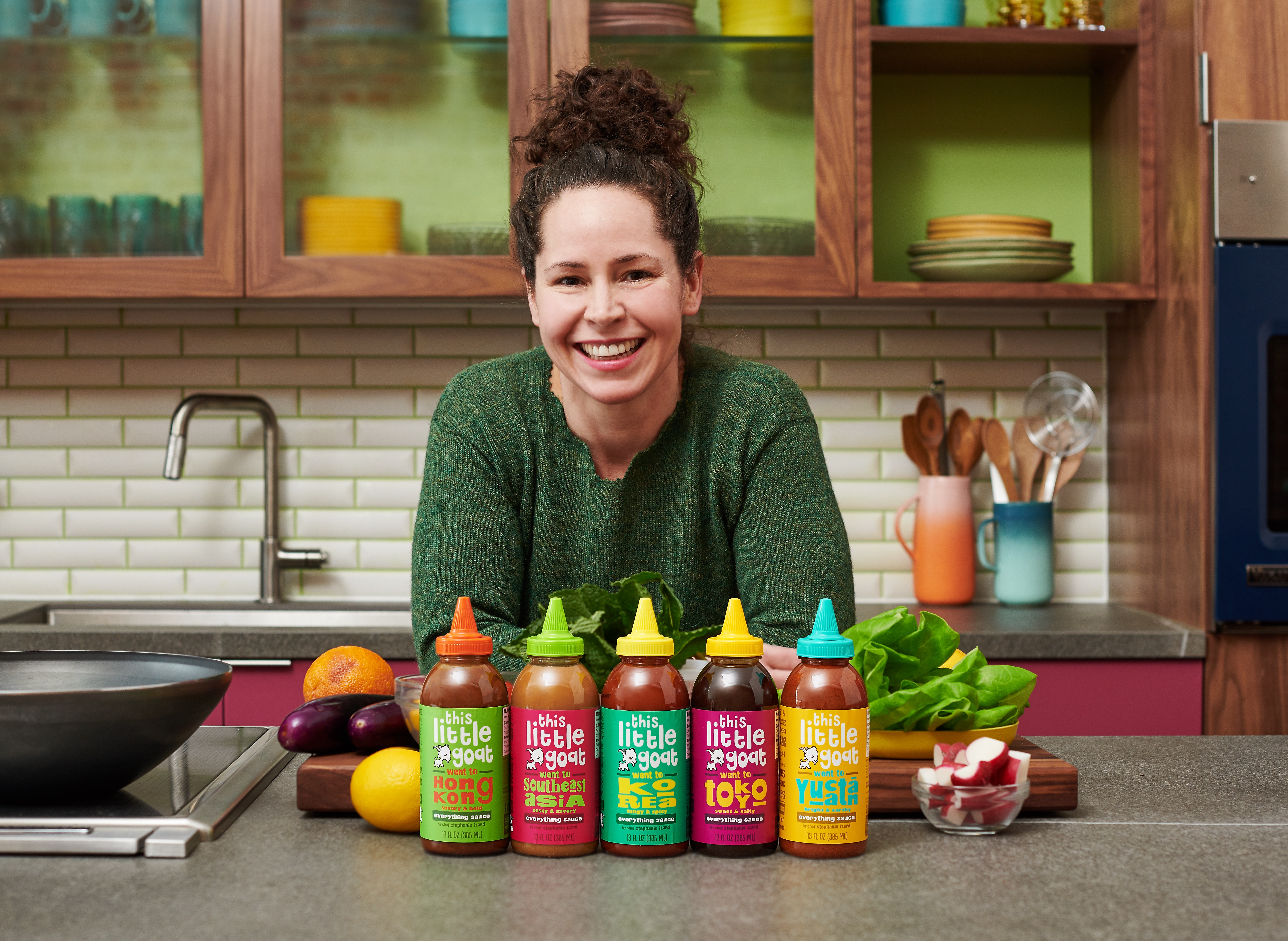 A smiling woman behind a row of bottled sauces