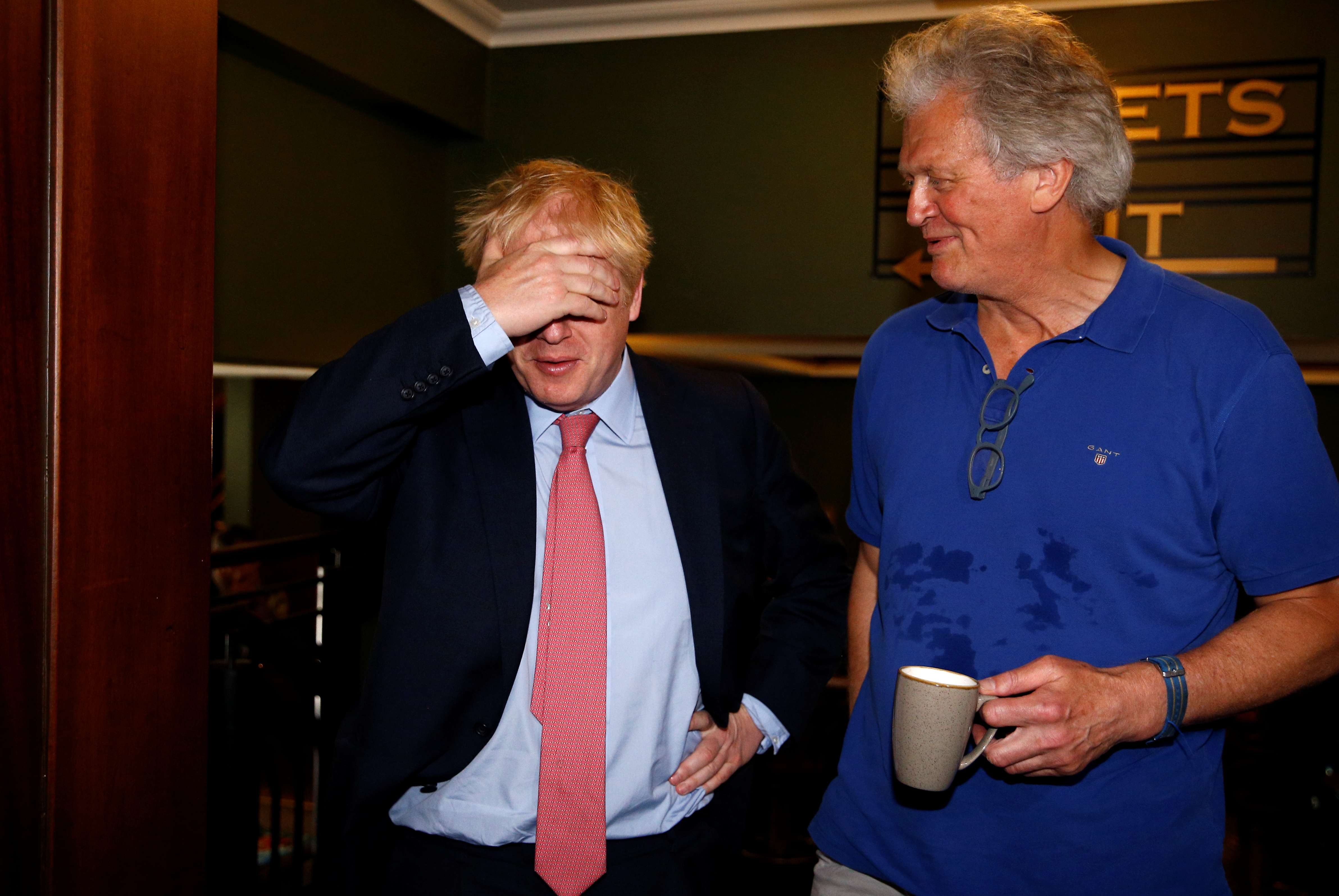 Boris Johnson covers his face while Campaigning In Central London with Tim Martin of Wetherspoons