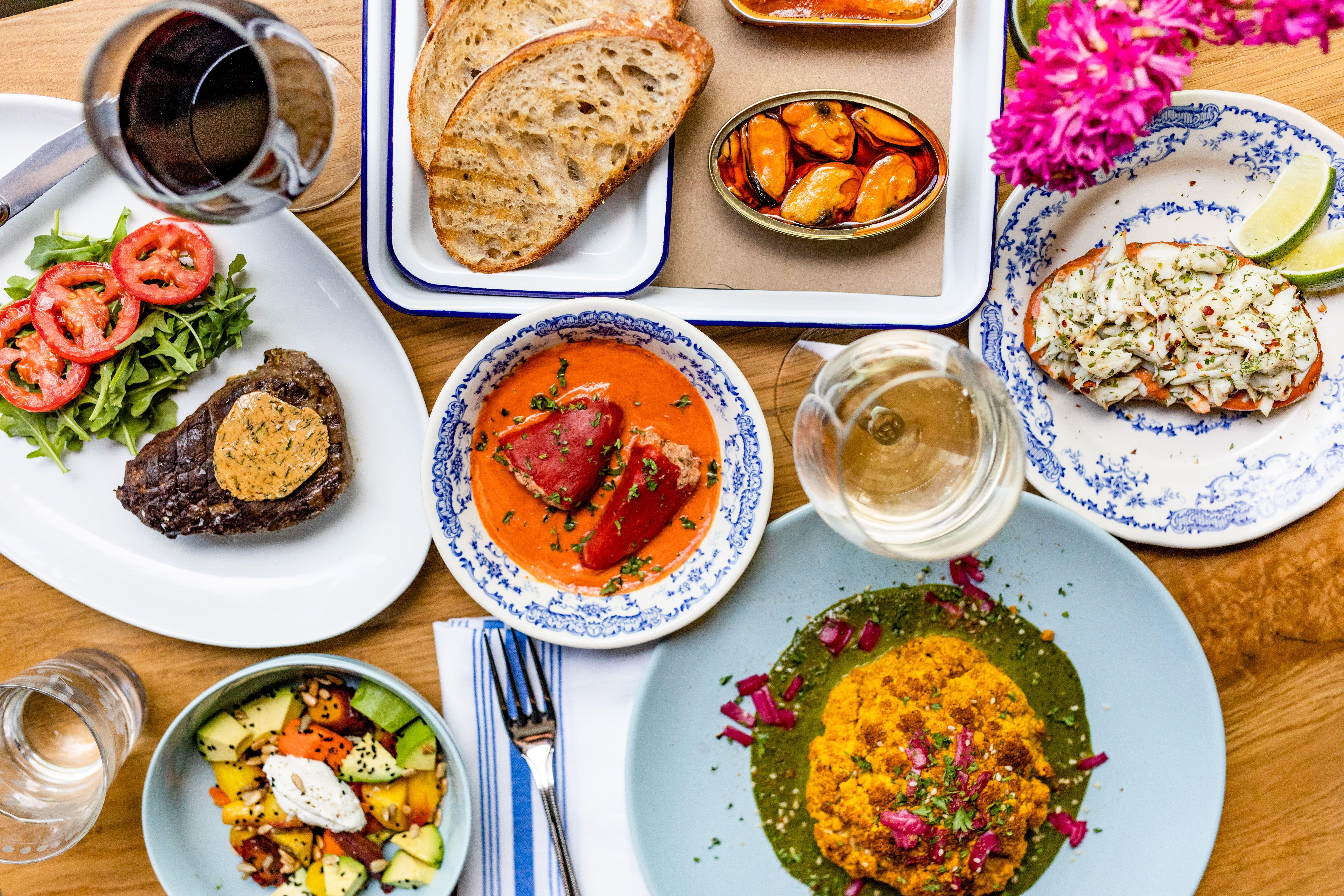 一种地中海食物,包括红辣椒汤、牛排、肌肉、新鲜面包和葡萄酒