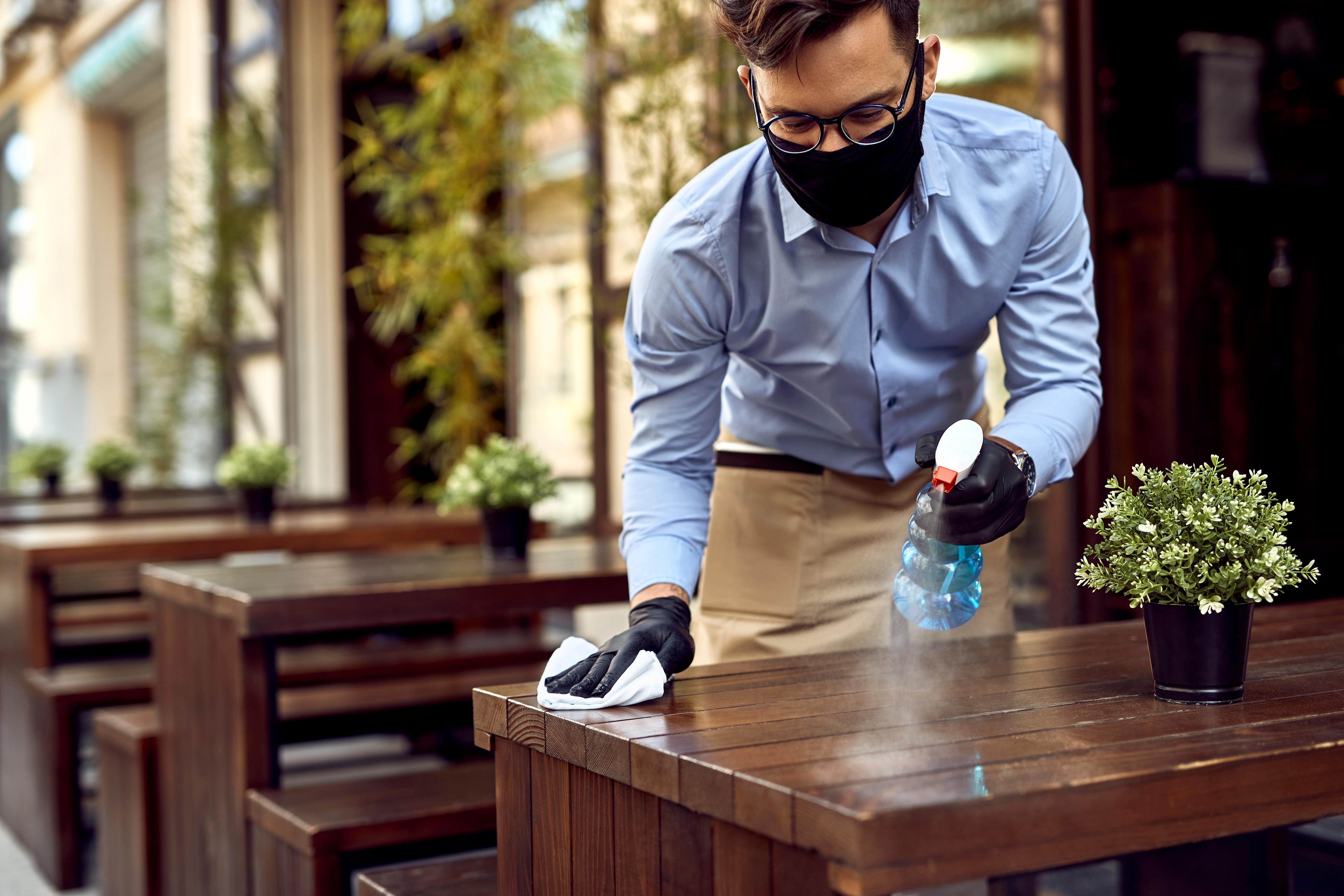 一位戴着眼镜、穿着蓝色衬衫的服务员戴着黑色的防护口罩在户外露台上为桌子消毒