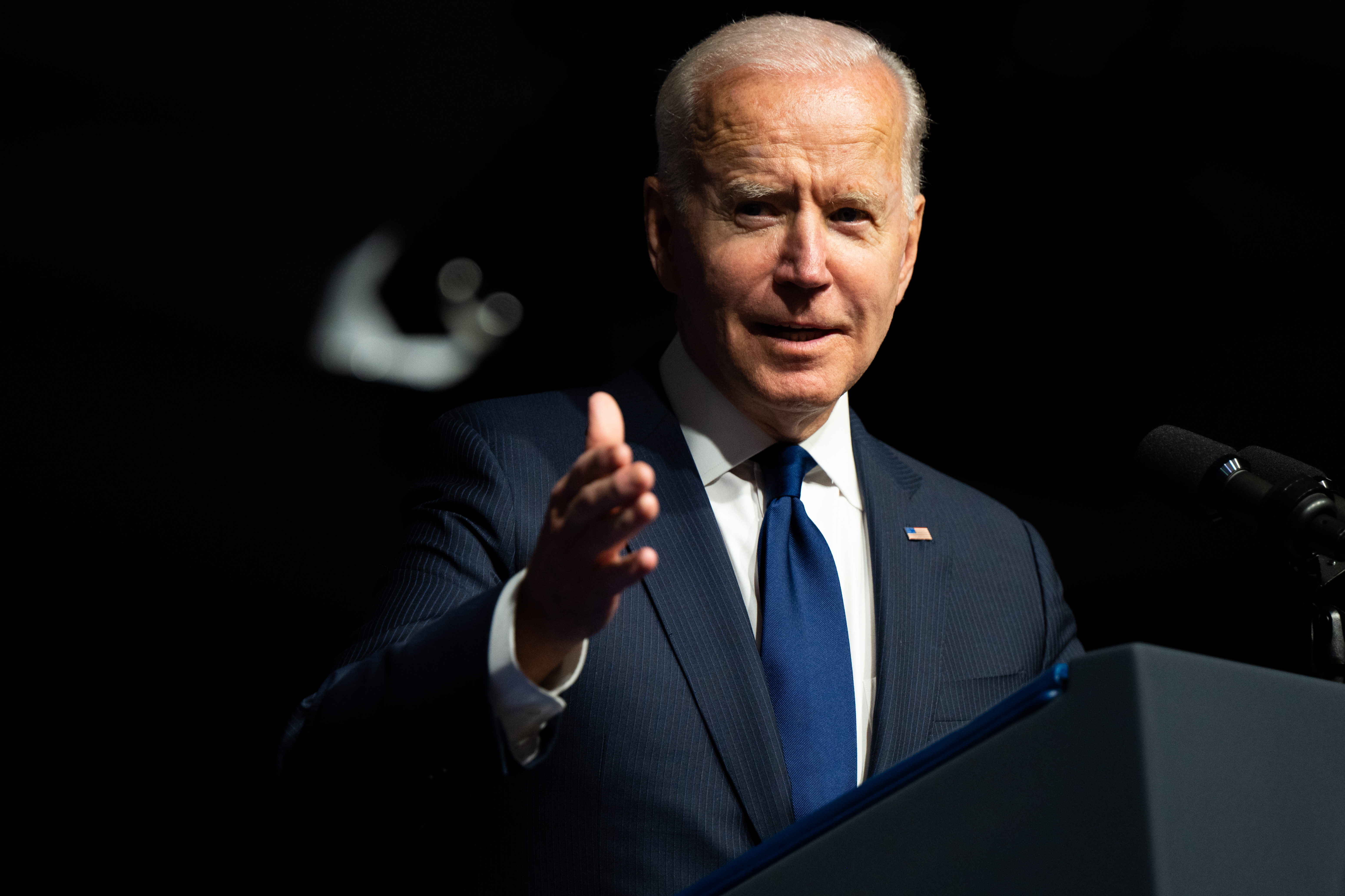 President Joe Biden stands at a lectern and gestures with his hand while speaking.
