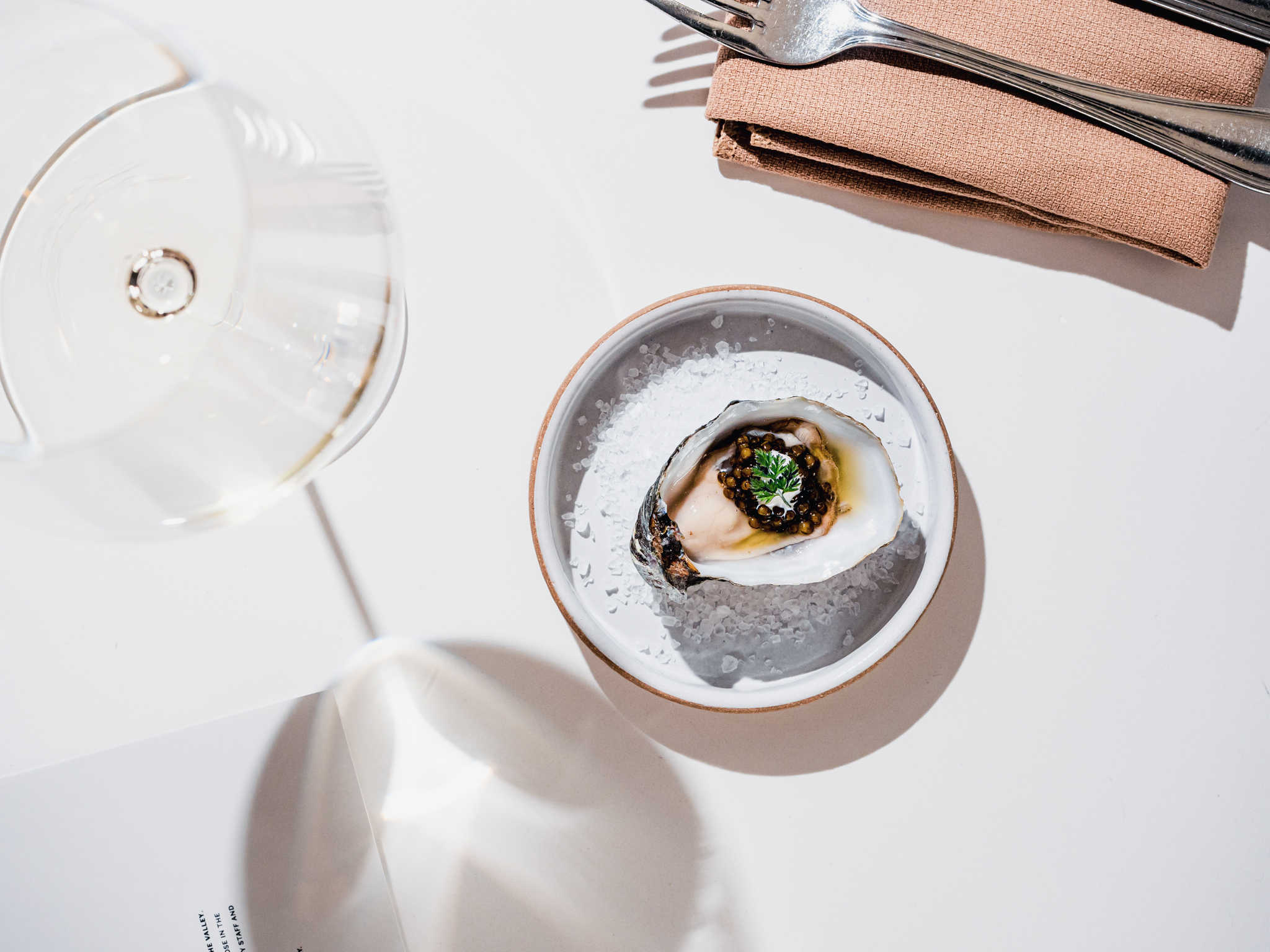 A single oyster topped with caviar and a pale white wine in a glass next to the plate.