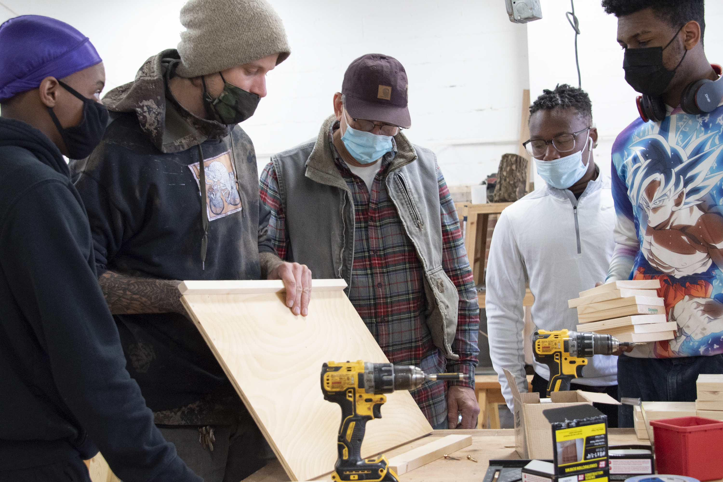 Students and adults work on building desks for remote learners