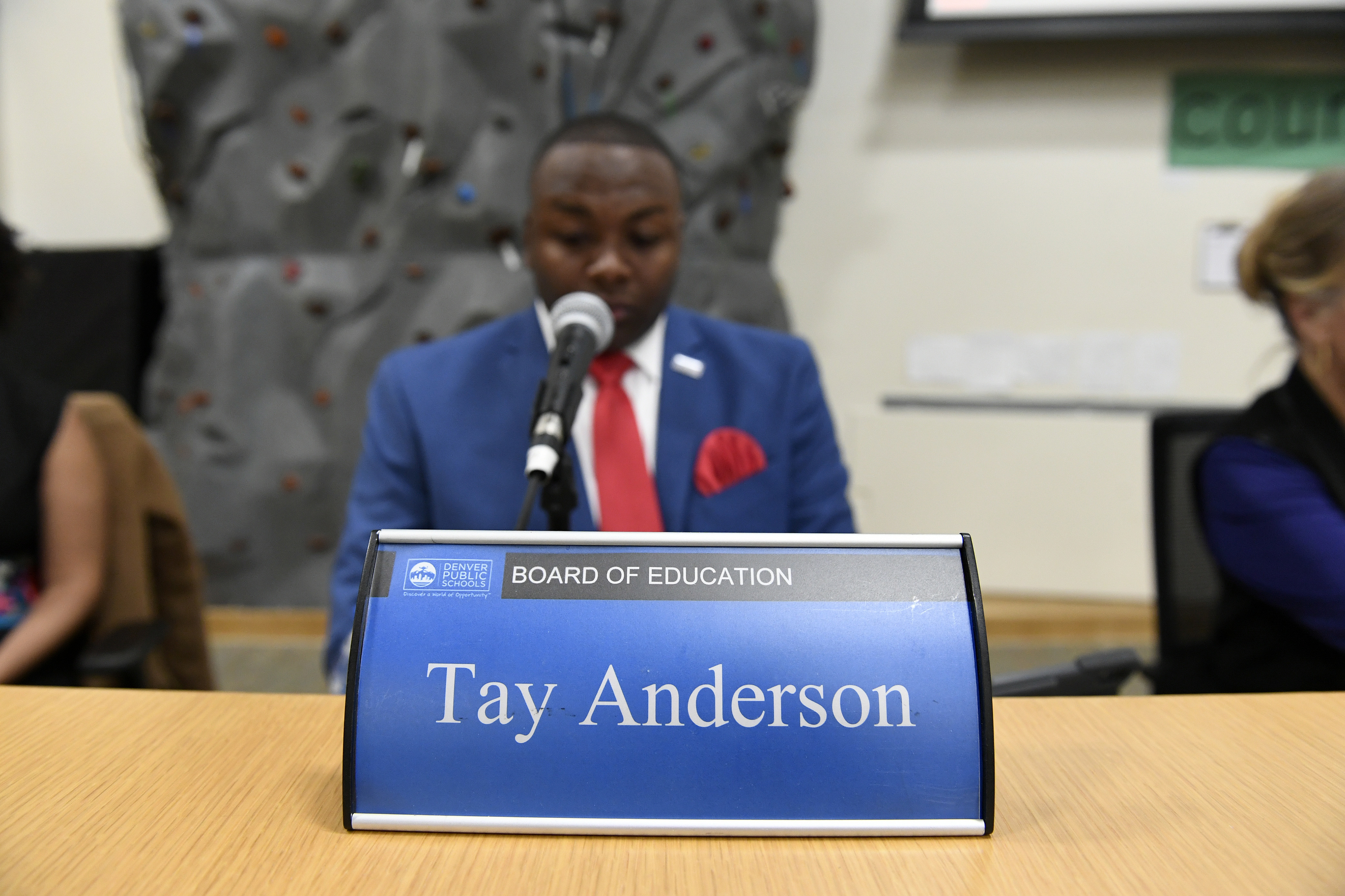Tay Anderson, wearing a red tie and blue suit, sits behind a blue placard with his name typed in white letters.