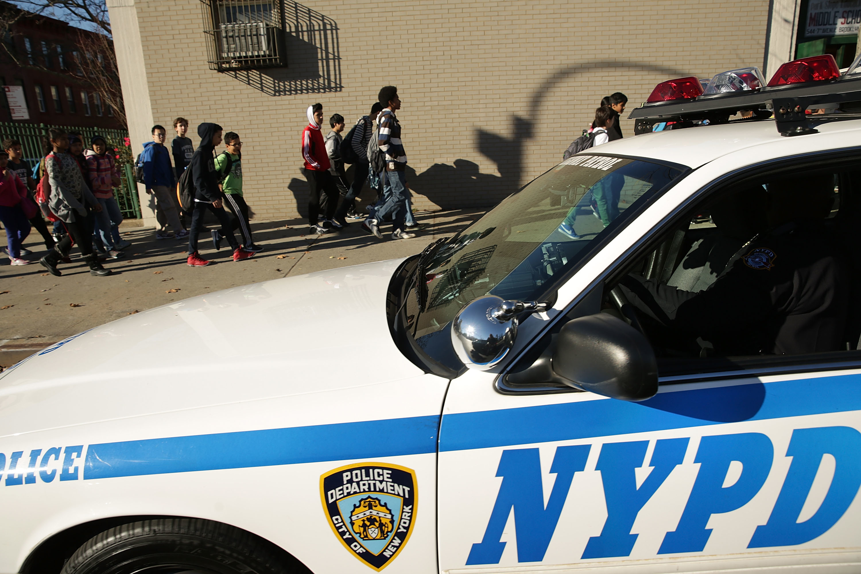 A New York Police Department cruiser sits in the foreground as students walk past on the sidewalk.