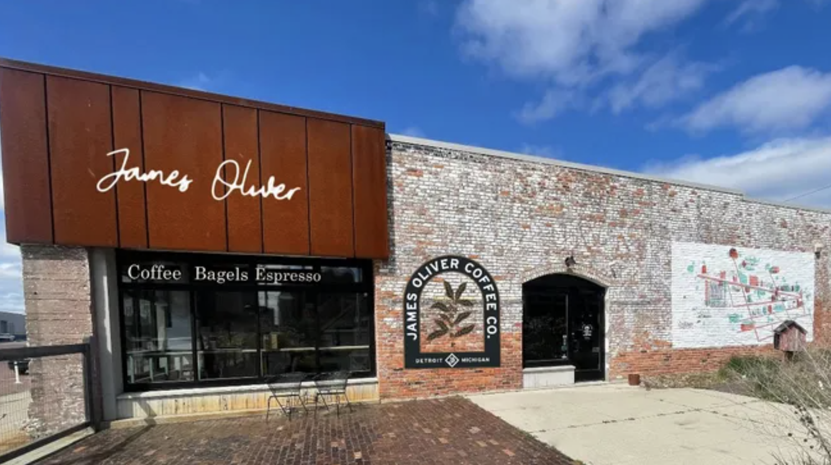 An artist's rendering of a brown commercial building in a storefront. There's a large glass window, and a sign atop a brown awning that reads James Oliver in cursive script.