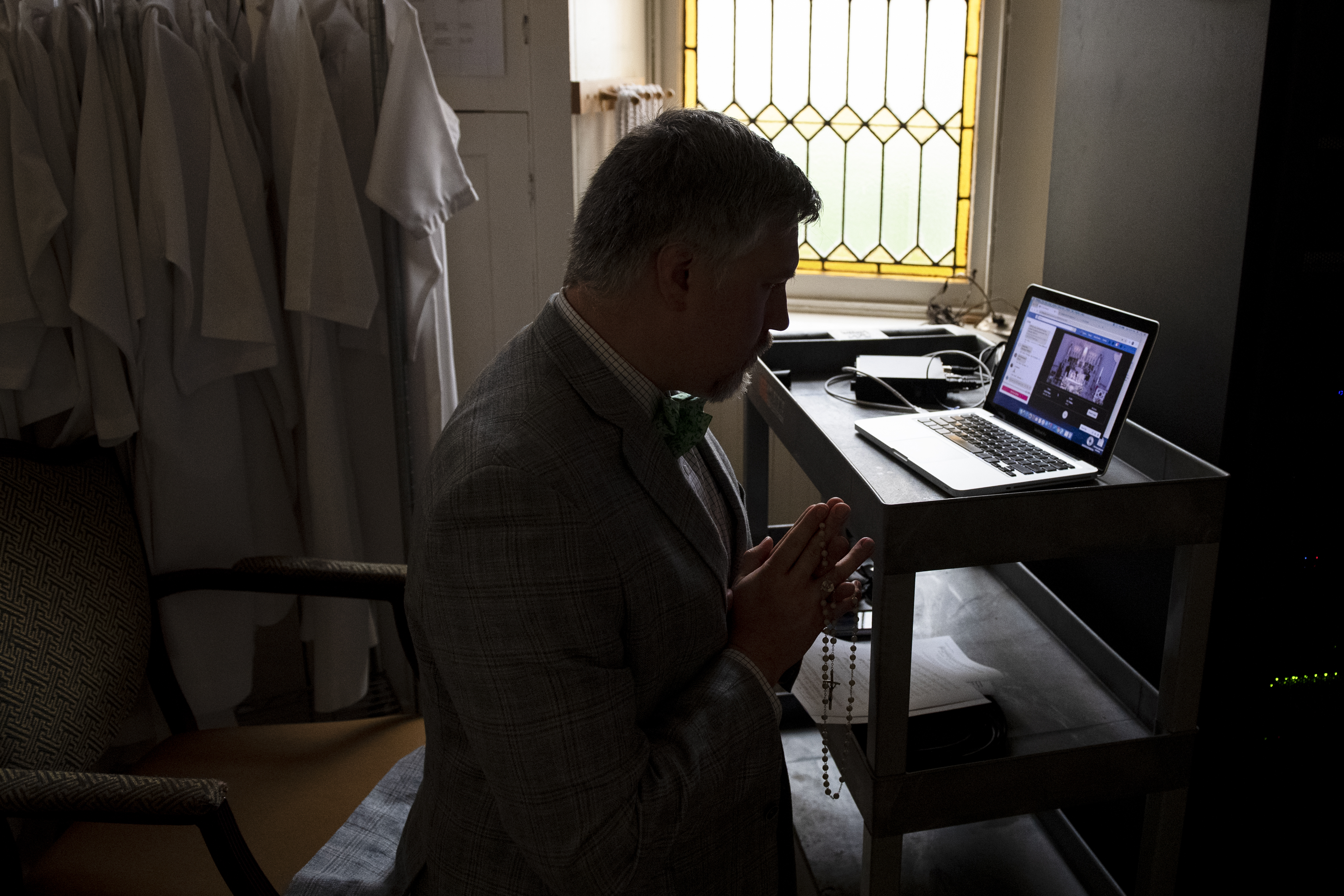 Otto Beck prays as he monitors a livestream of an Easter Vigil Mass in a parlor adjacent to the sanctuary at Saint Peter's Church on Capitol Hill without worshipers due to the coronavirus outbreak on Sunday, April 12, 2020.