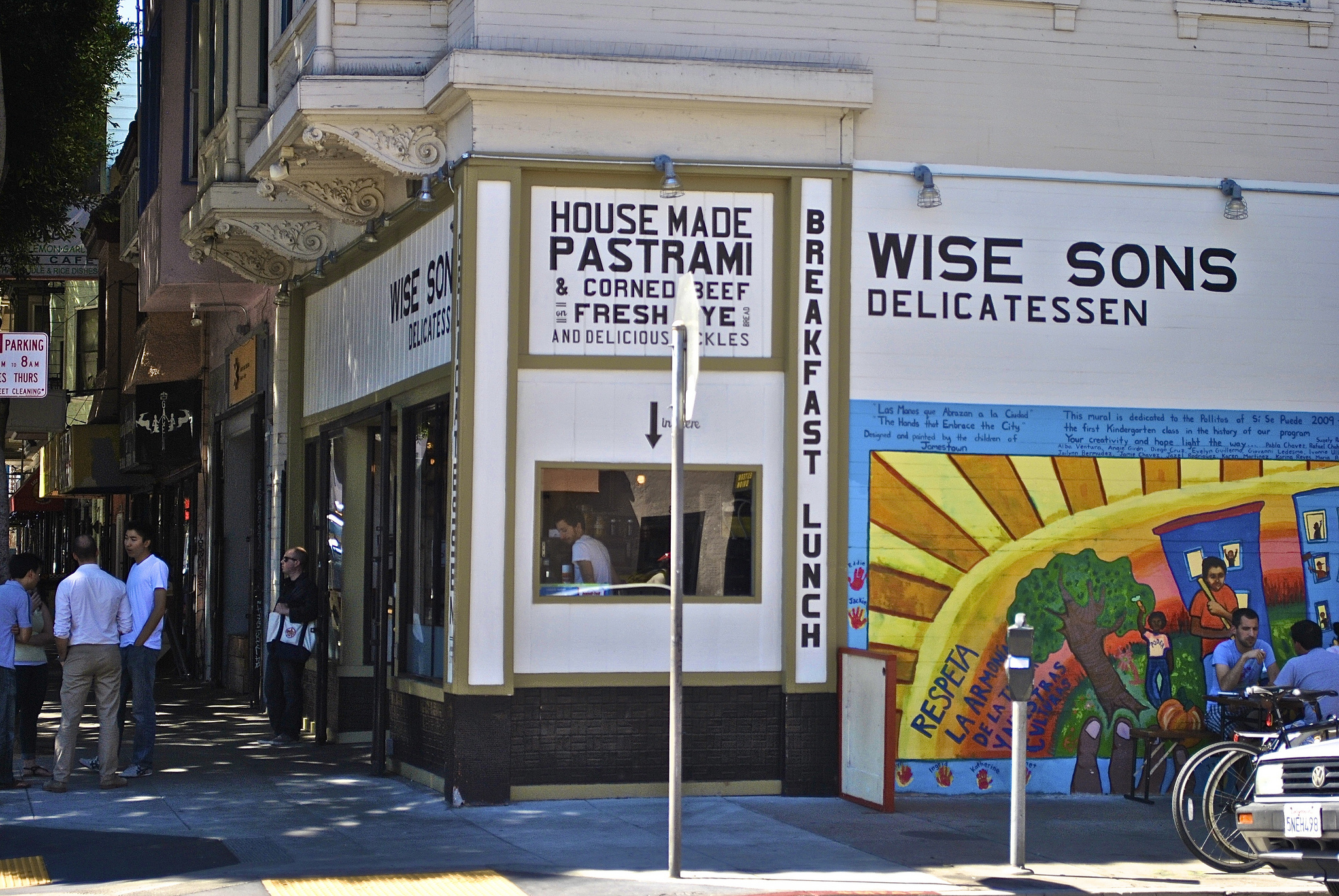 Exterior of Wise Sons Delicatessen with outdoor dining and a line out front