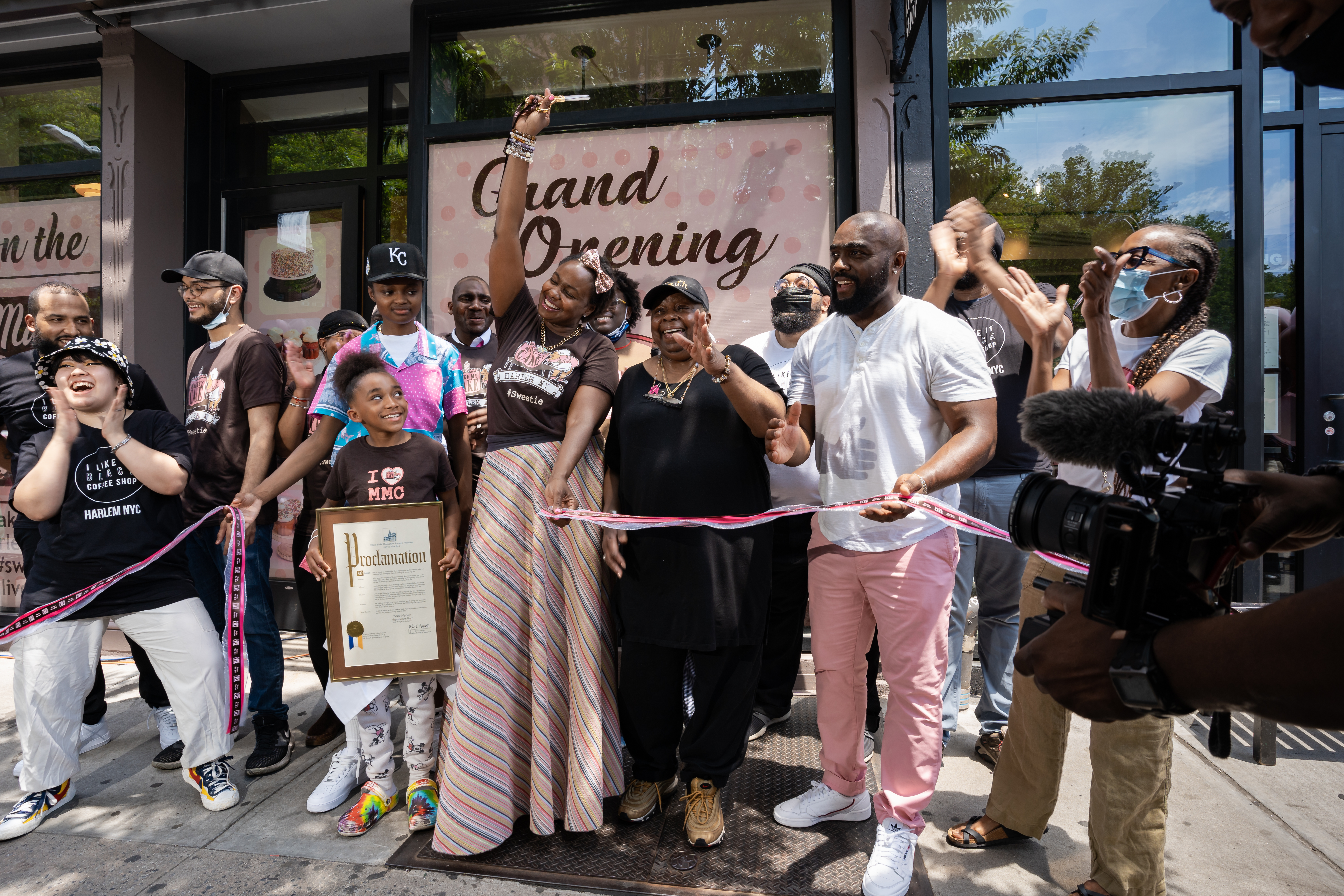"""A group of people celebrate a ribbon cutting in front of a restaurant, whose sign reads """"Grand Opening"""" in cursive font"""