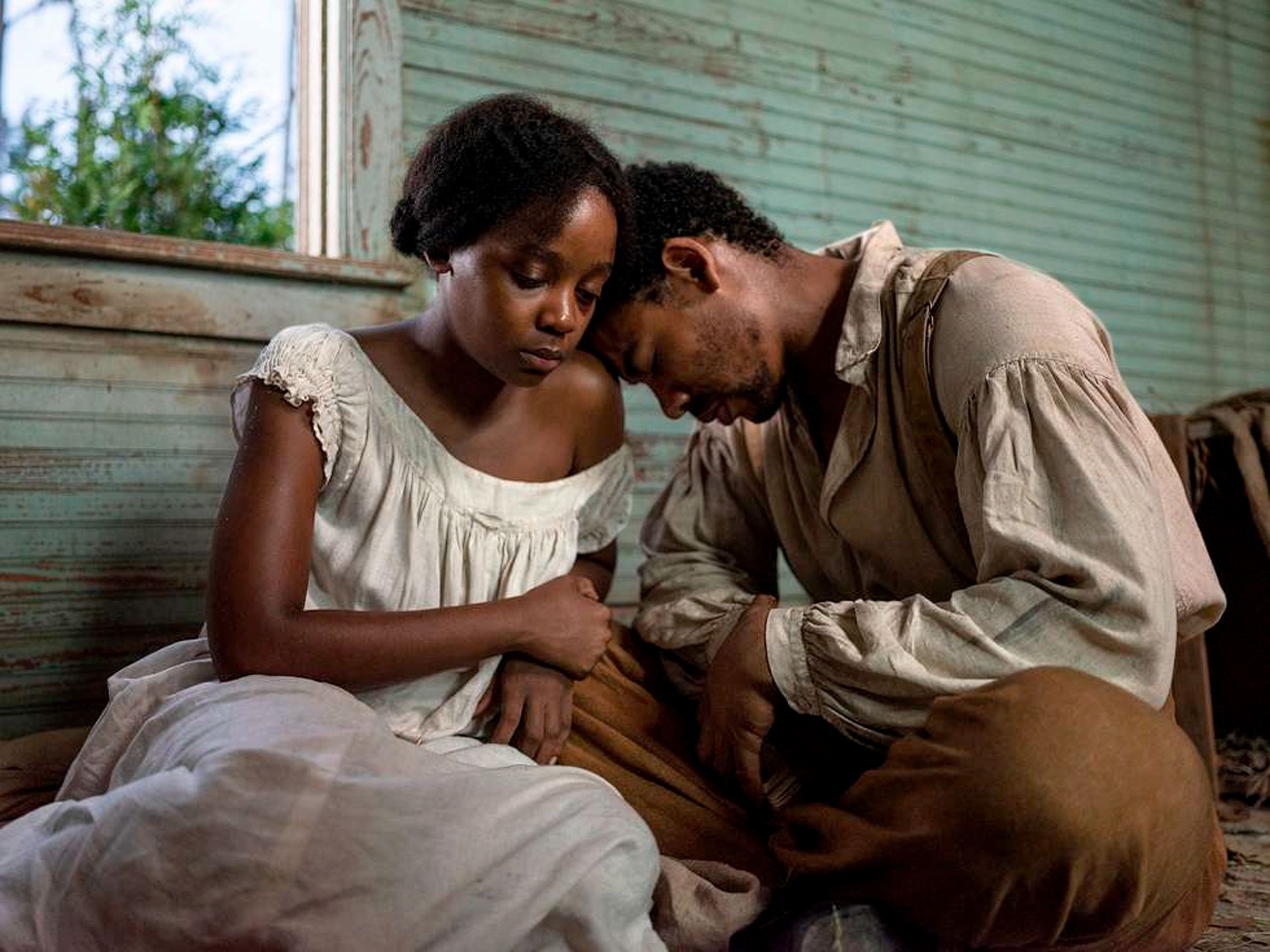 Two Black characters sit by an open window with their heads together in Barry Jenkins' The Underground Railroad