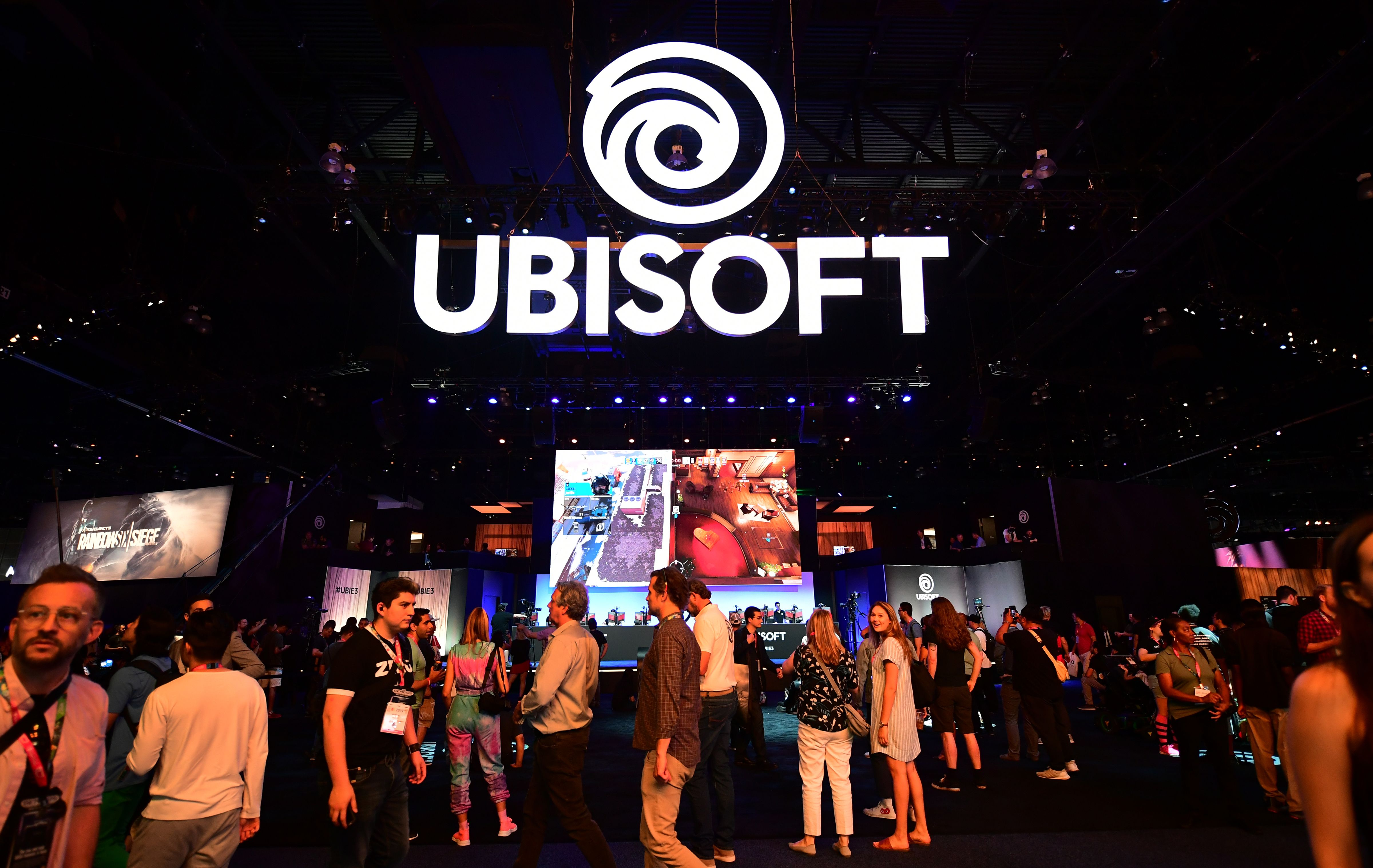 people standing below a Ubisoft logo at the company's E3 2019 booth