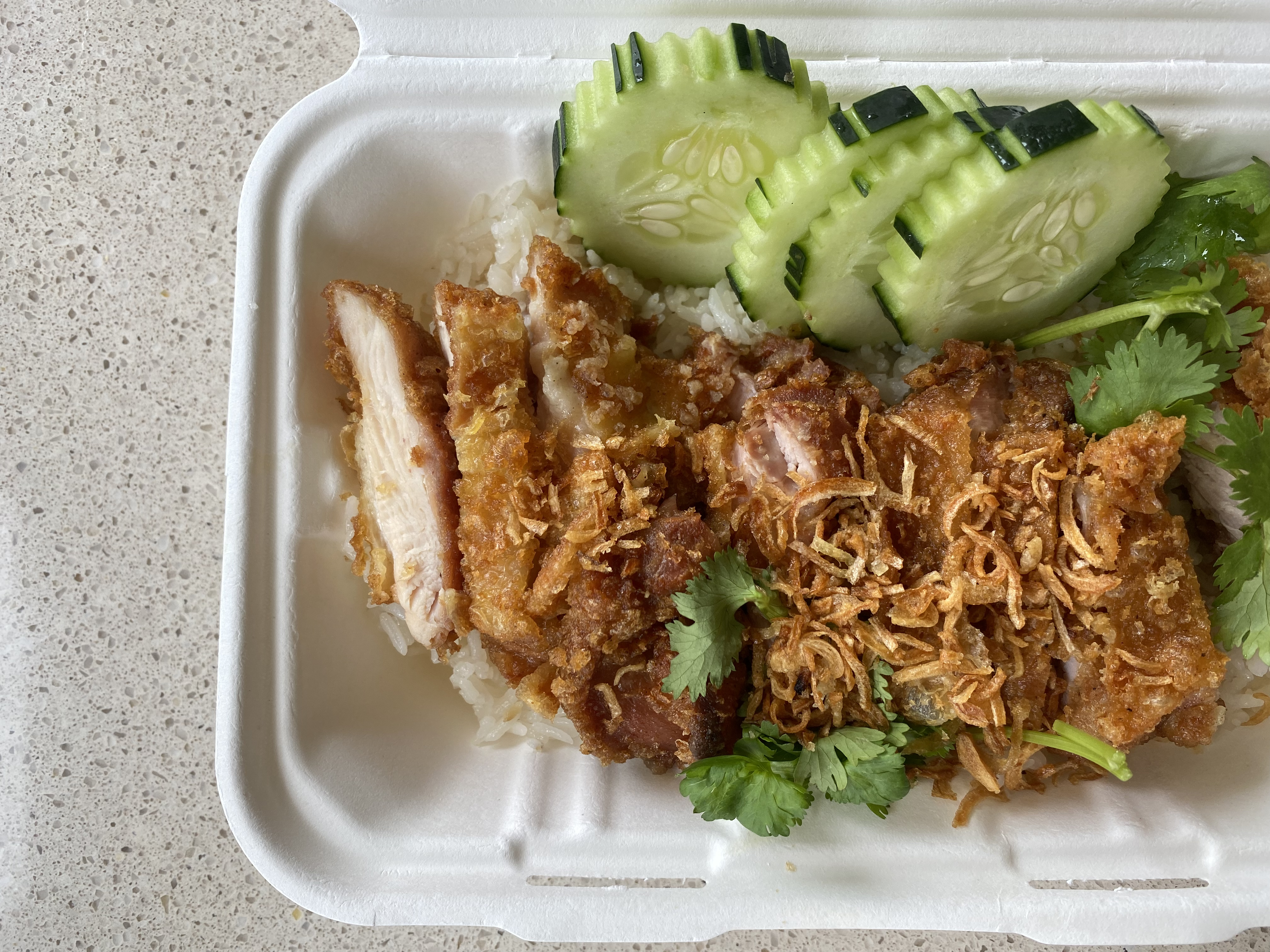 Sliced golden fried chicken sits next to cucumbers and over a pile of rice; springs of verdant cilantro are scattered about