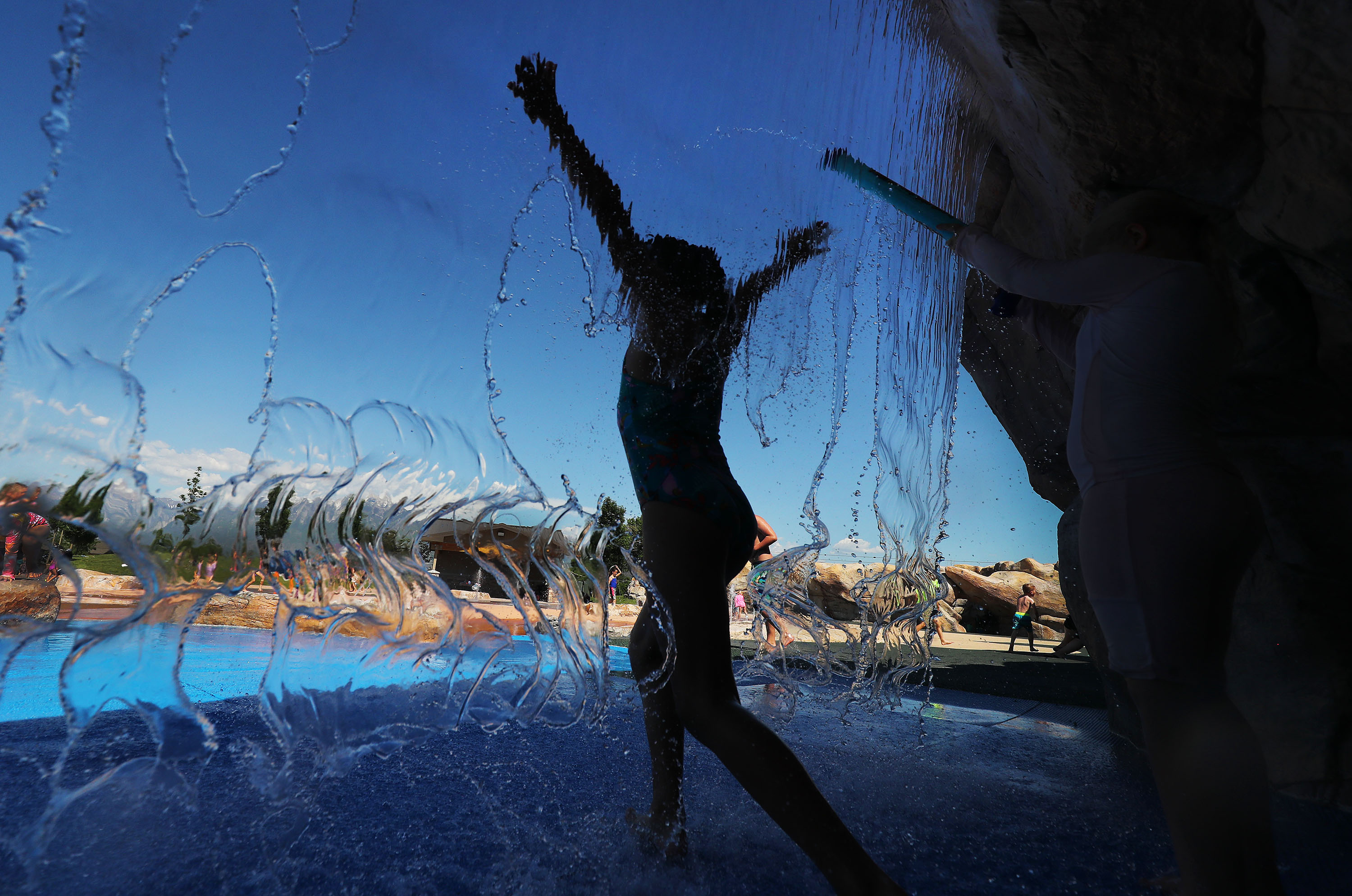 Children cool off in the water at Wardle Fields Regional Park splash pad in Bluffdale on Thursday, June 3, 2021.