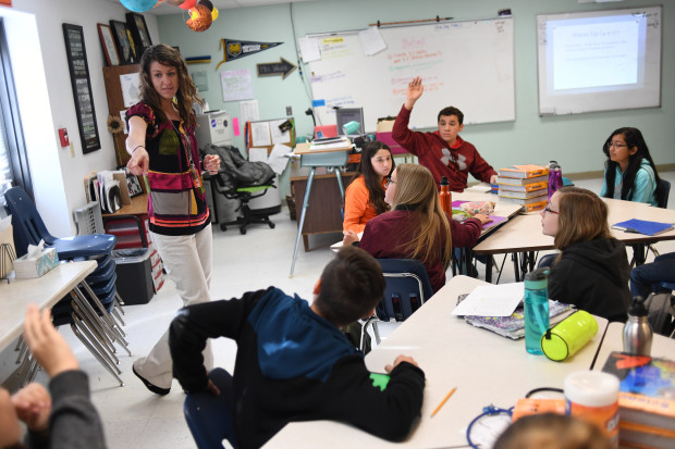 Stephanie Wujek teaches science at Wiggins Middle School, on April 5, 2017 in Wiggins, Colorado. A woman with shoulder-length brown hair stands at the front of the classroom and points to a student. Other students sit at tables, and one in a red hoodie raises their hand.