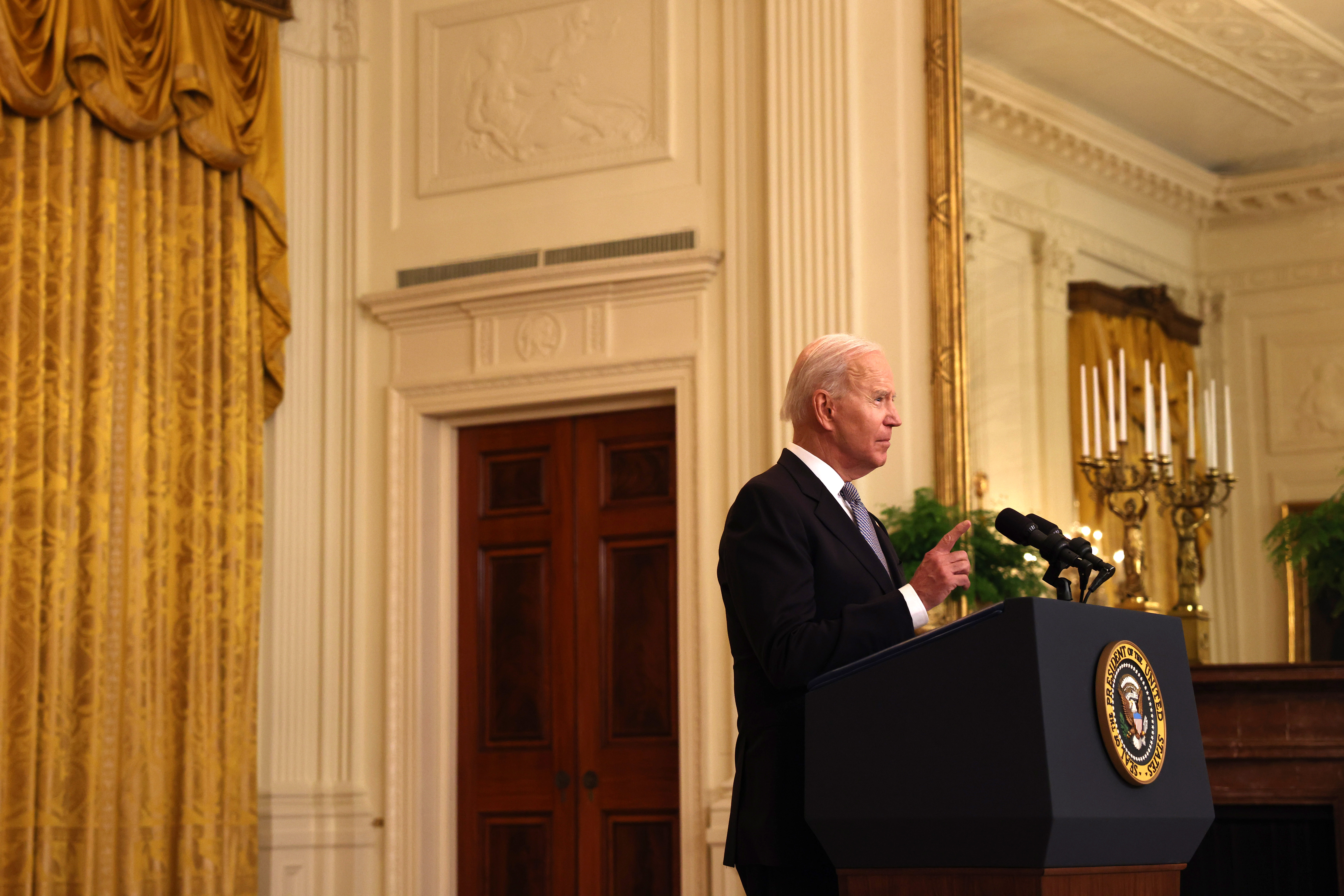 President Joe Biden speaks at a podium marked with the Presidential seal in a room with golden drapes and a large candelabra behind him.