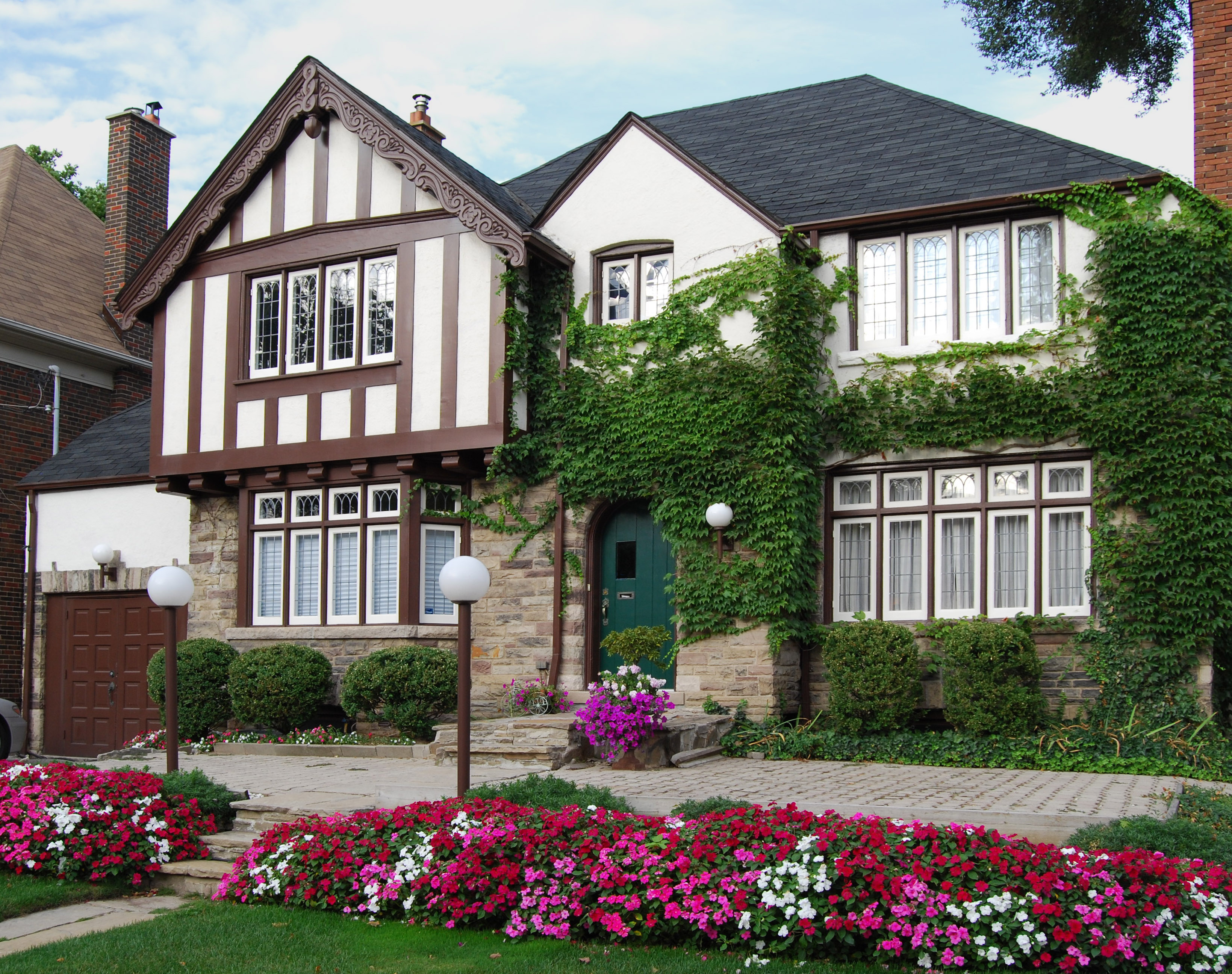 A tudor style house with brown trim, green ivy, and pink flowerbeds.