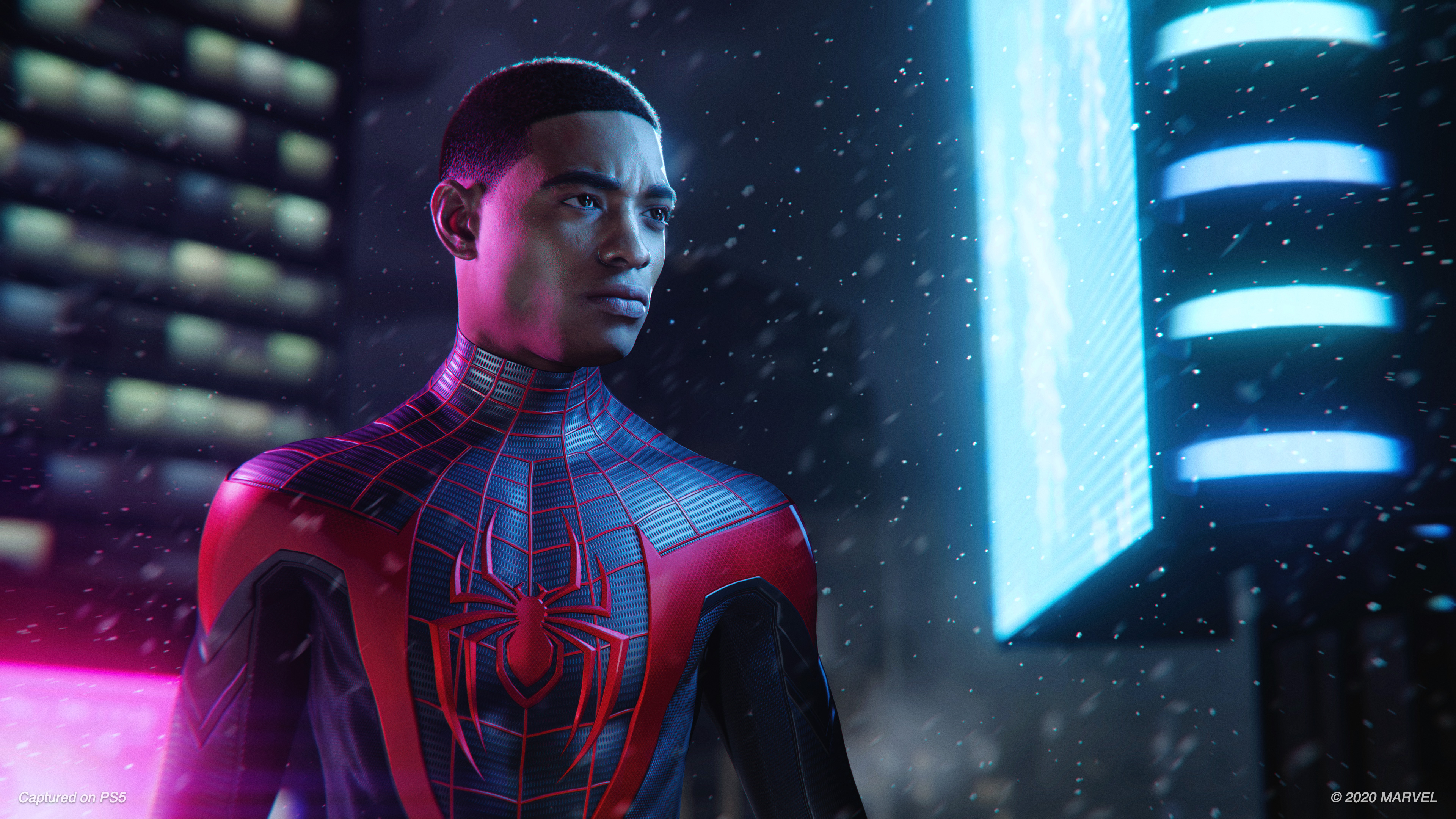 an unmasked Miles Morales wearing the Spider-Man suit in Spider-Man: Miles Morales