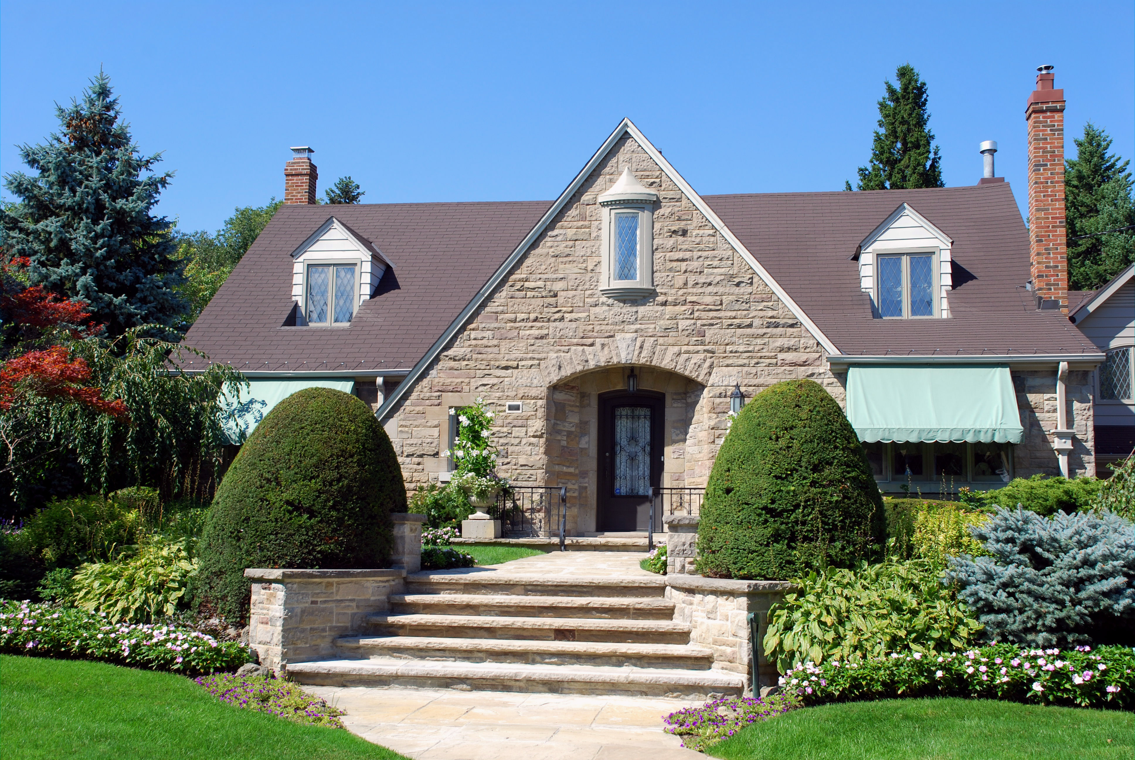 A stone house with large stone front porch, green yard, and colorful flowerbeds.