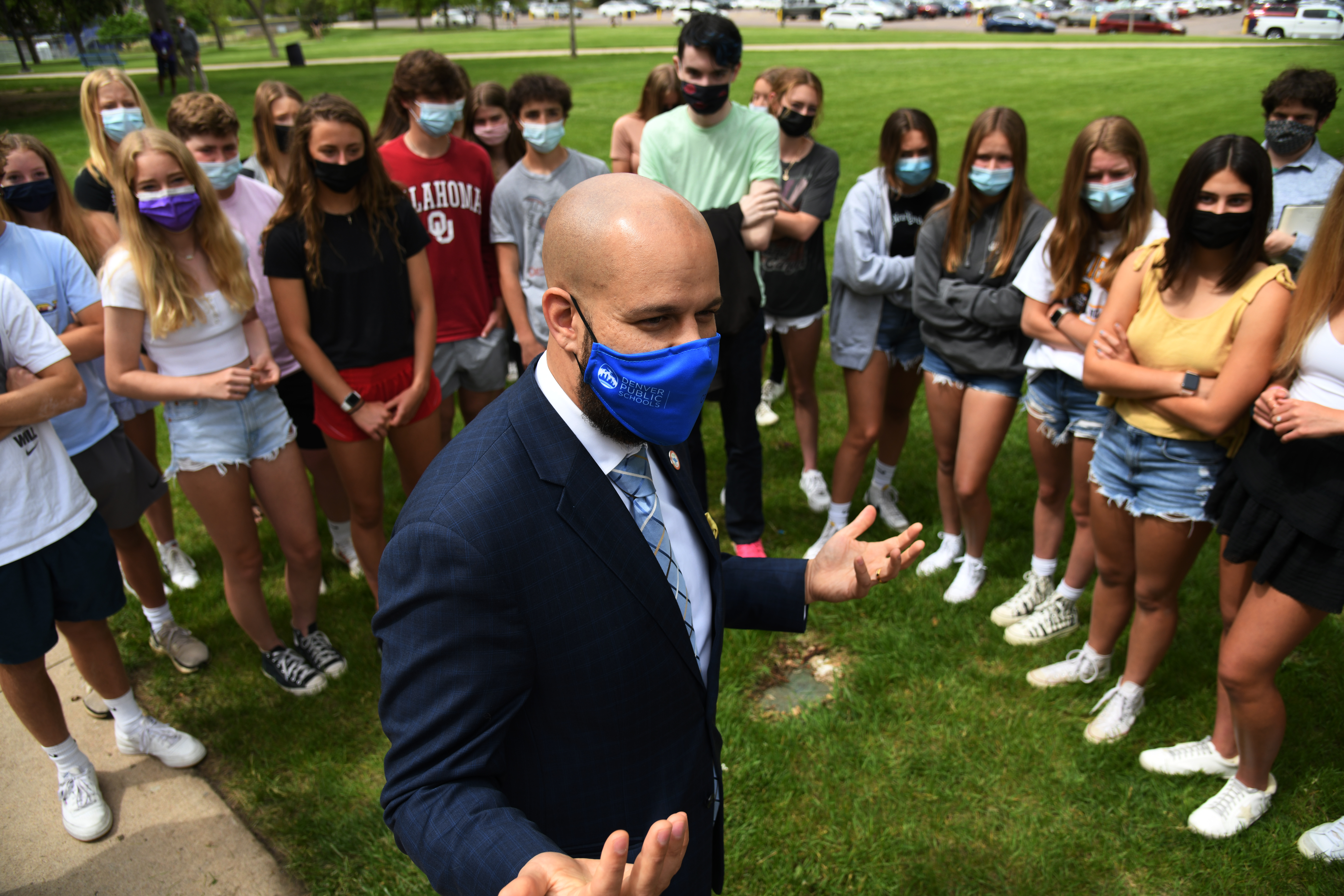 Alex Marrero, standing outside on grass and wearing a mask, is surrounded by masked high school students listening to him talk.