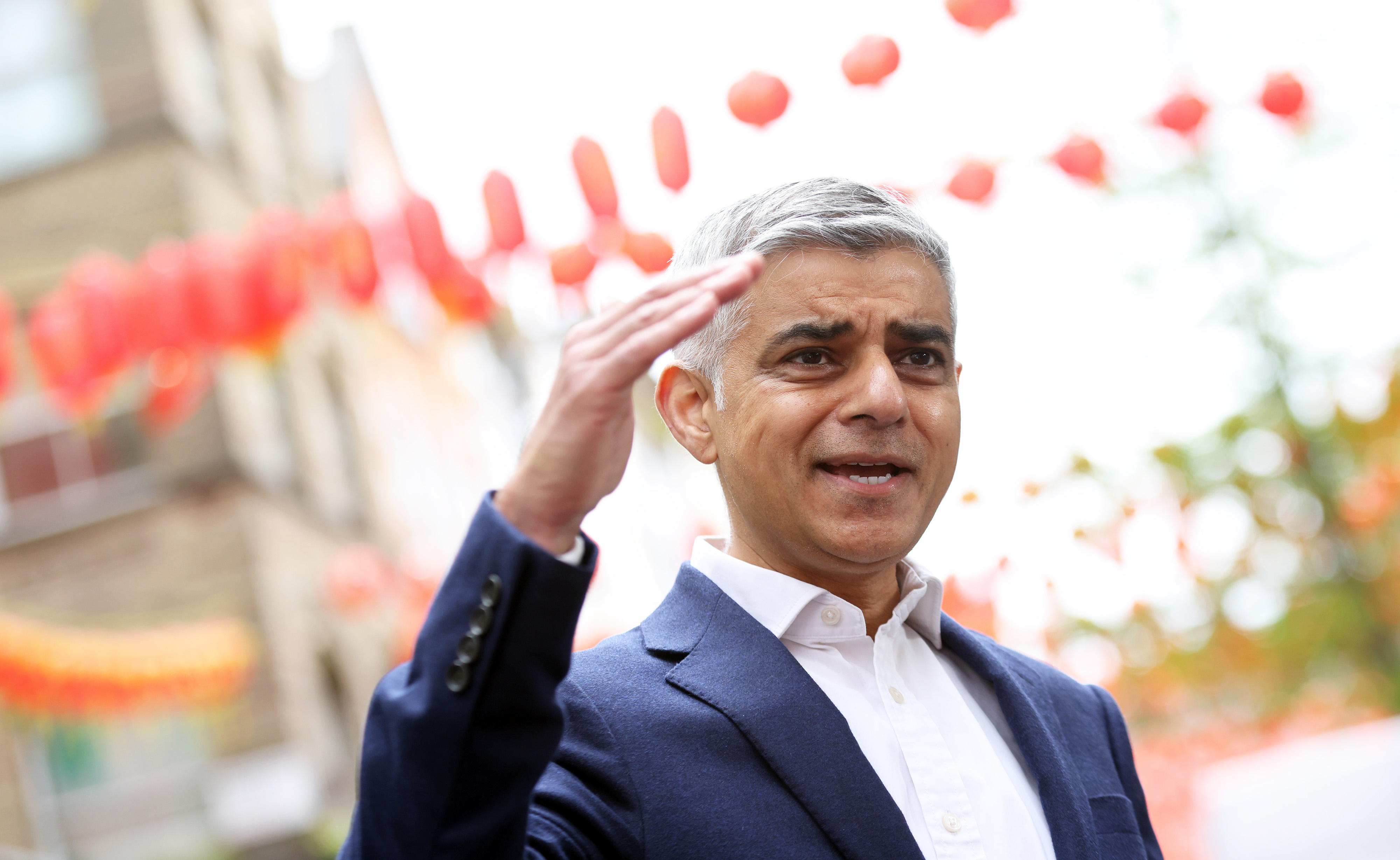 Mayor of London Sadiq Khan stands in Chinatown on the day indoor dining resumed in London with his right hand raised.