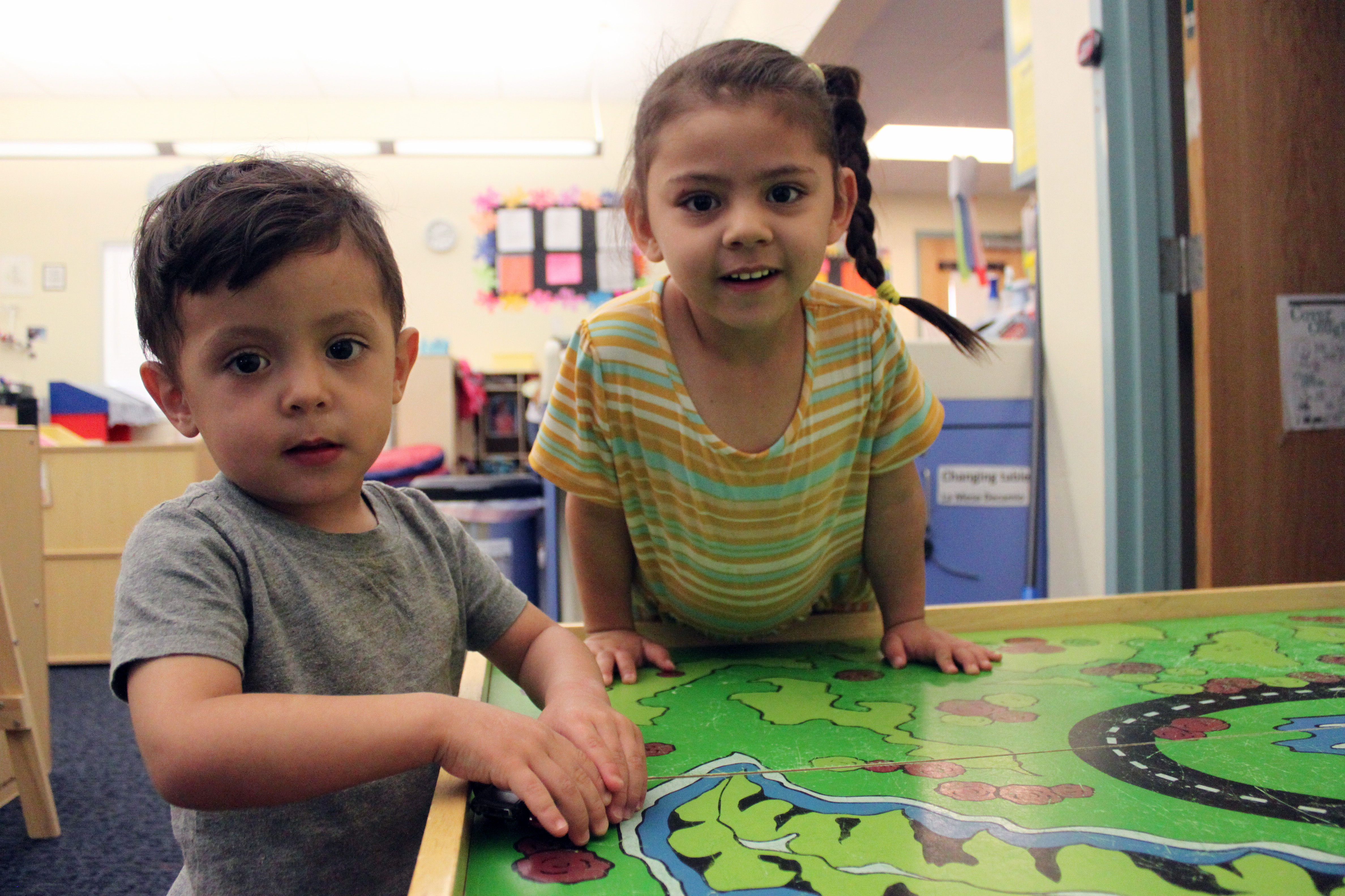 Arelyanna, 3, and Javier, 2, play with toy cars to at Cuidando Los Ninos in Albuquerque, N.M.