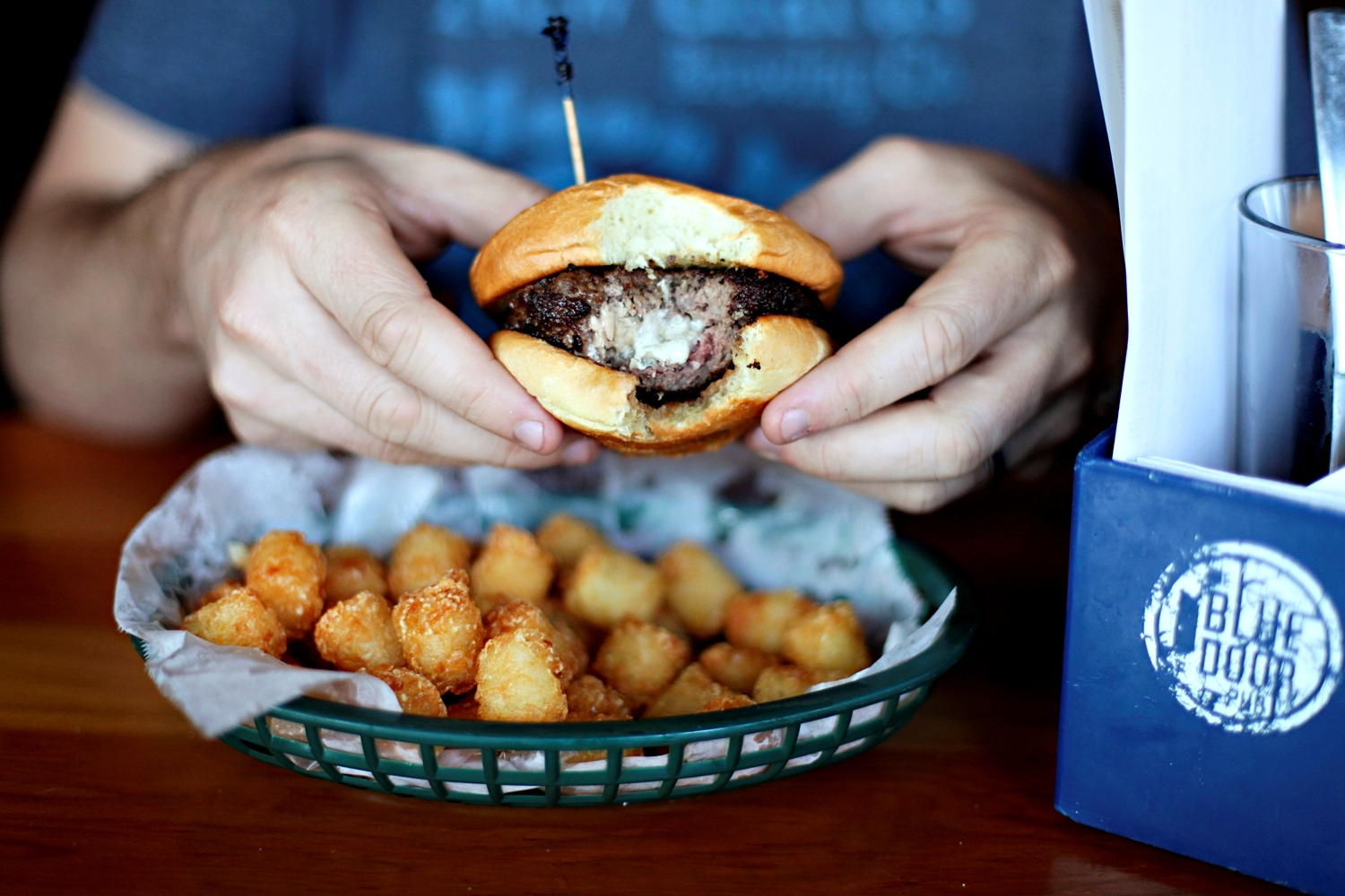 A person holding a burger with a bite out of it, cheese is oozing out of the center