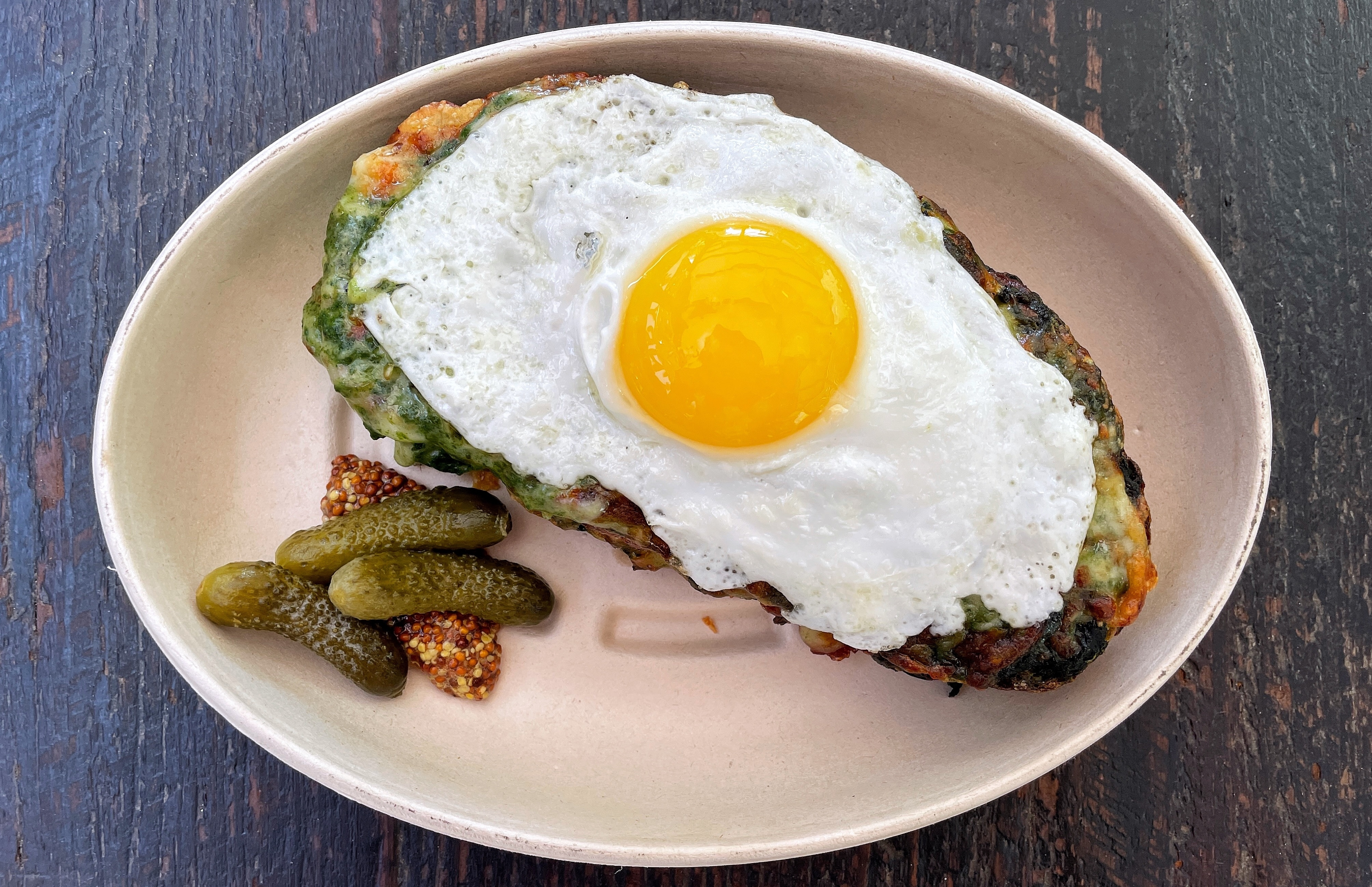 An overhead shot of Dirt Candy's spinach croque monsieur, a sandwich topped with a fried egg, in a takeout container.