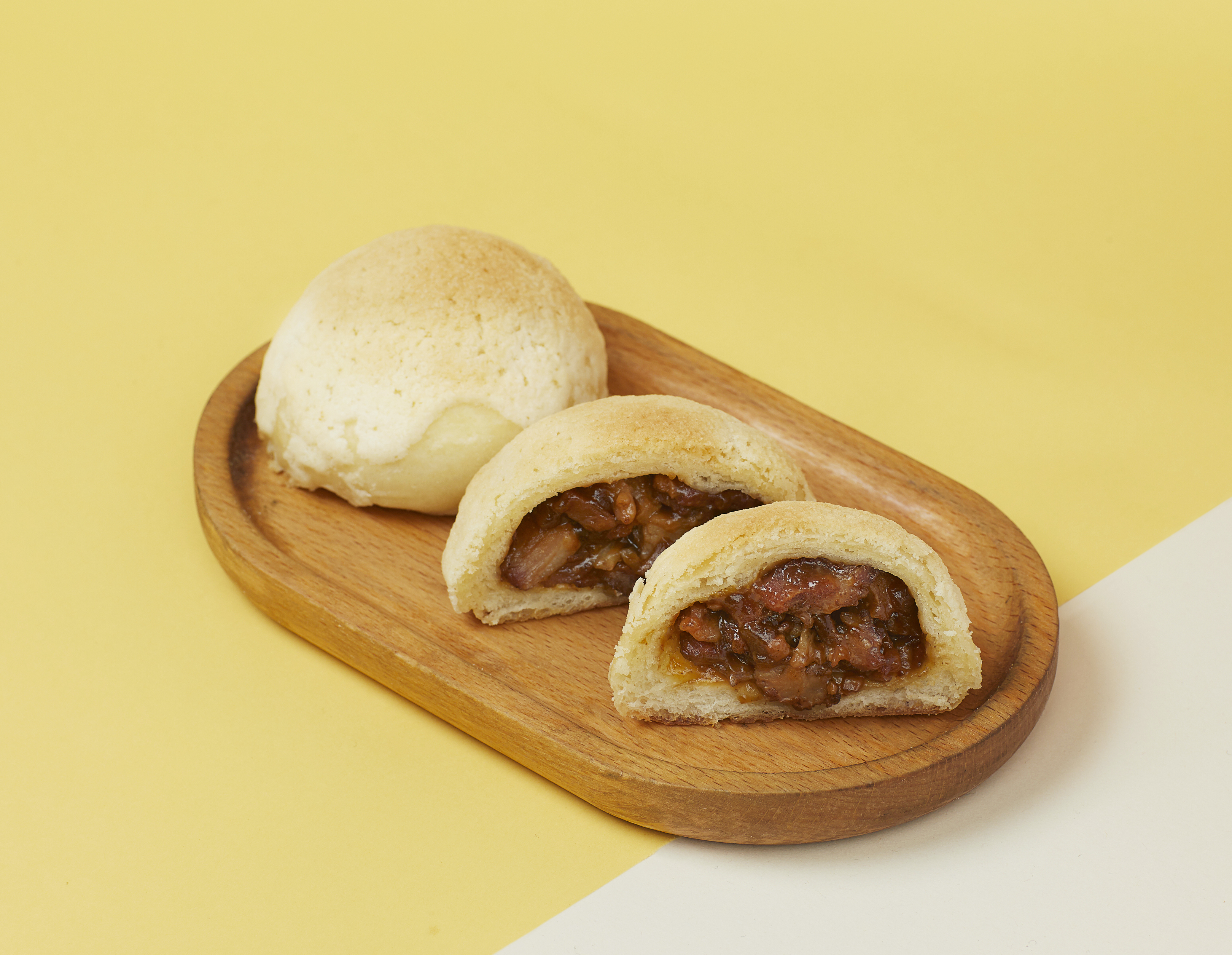 Two bao buns, one cut in half to show pork stuffed inside, sit on a wooden platter against a yellow and white background
