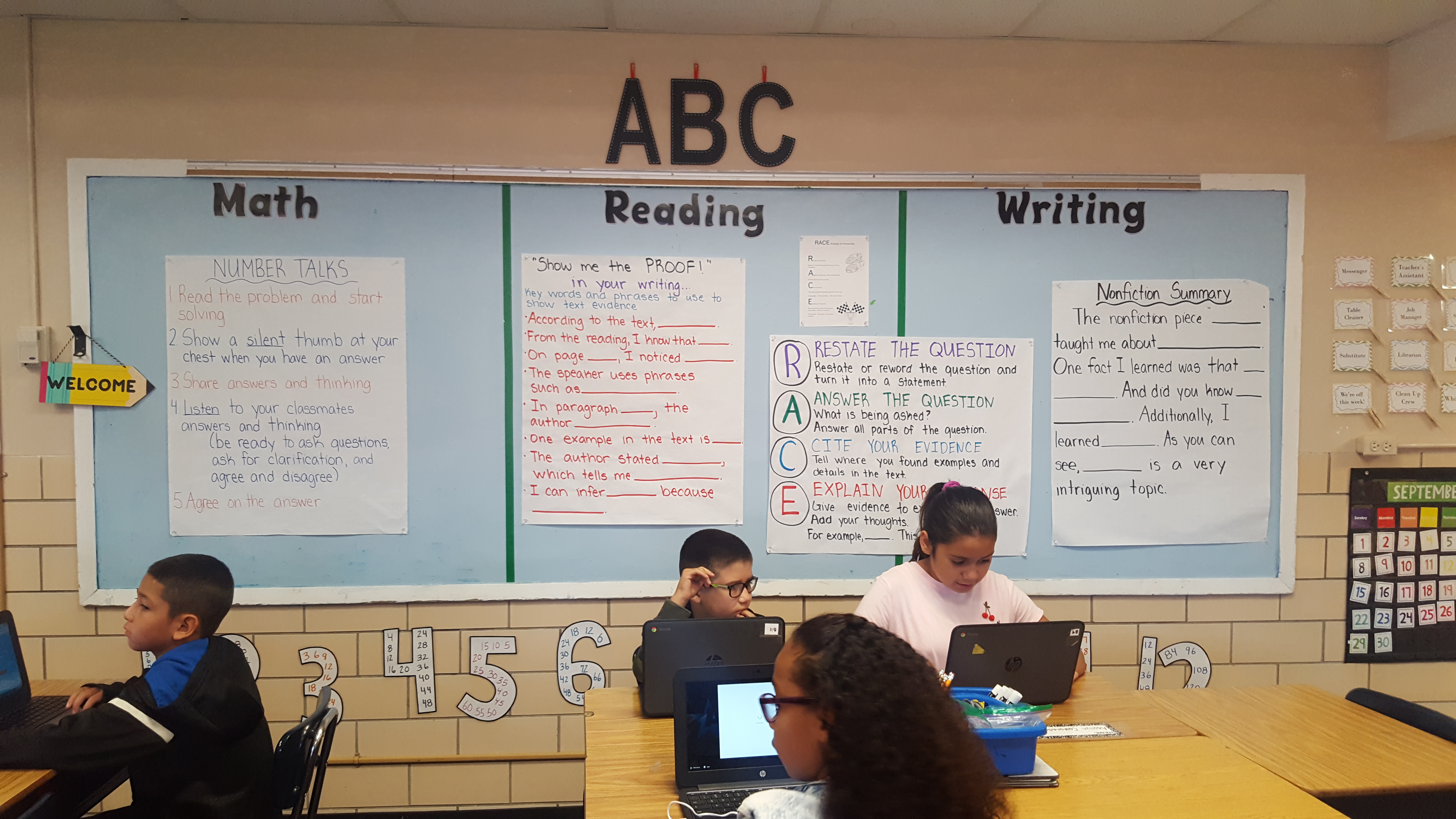 Elementary students work at their desks. The wall behind them is decorated with math, reading, and writing lessons. Large letters ABC are above.