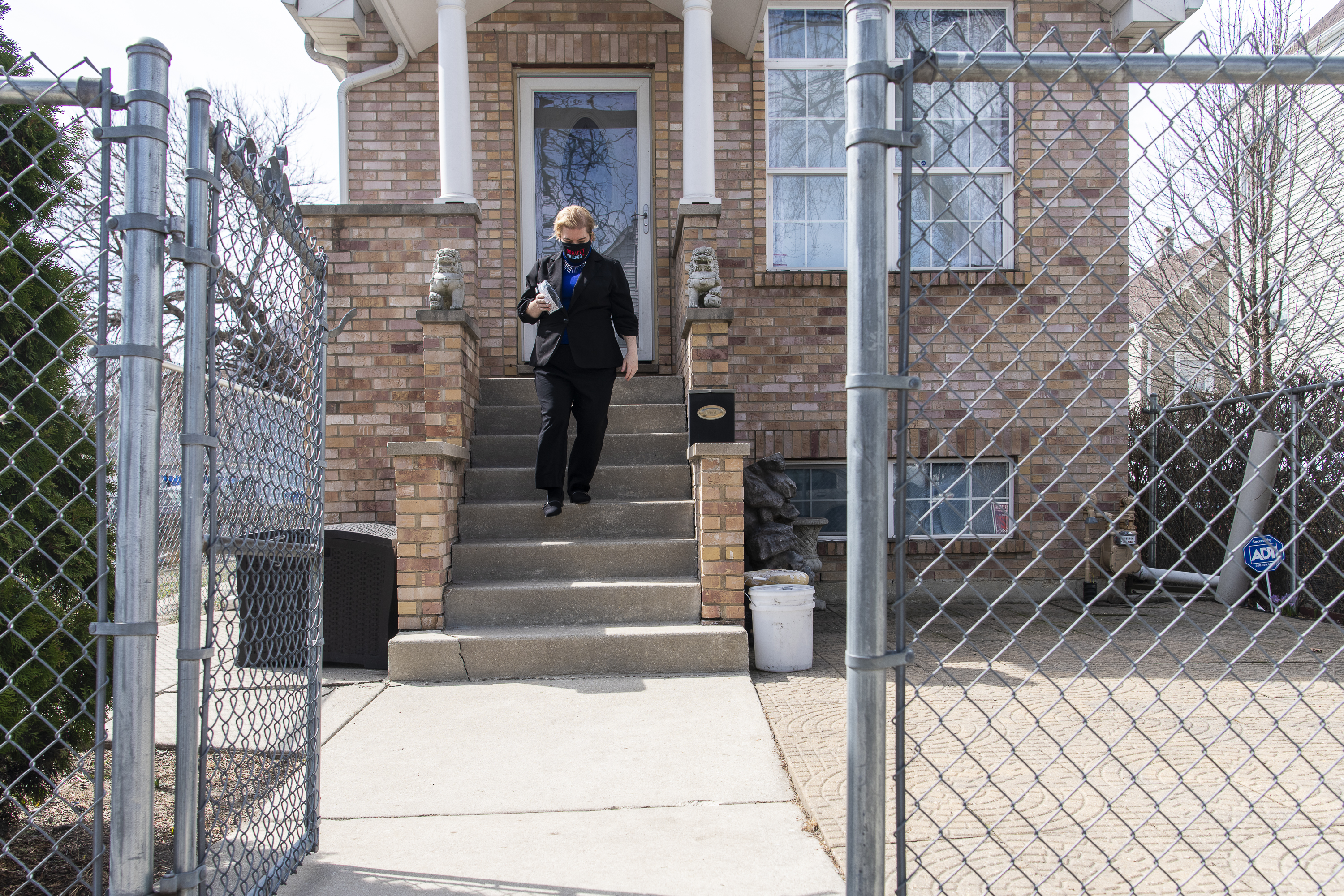 Dr. Allison Arwady walks away from a home in the Back of the Yards neighborhood in March during a canvassing event to share information on COVID-19 vaccines. Vaccine ambassadors will be in 13 Chicago neighborhoods this weekend.