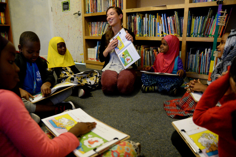 A young woman smiles as she shows a picture book to a group of young children seated in a circle beside her.