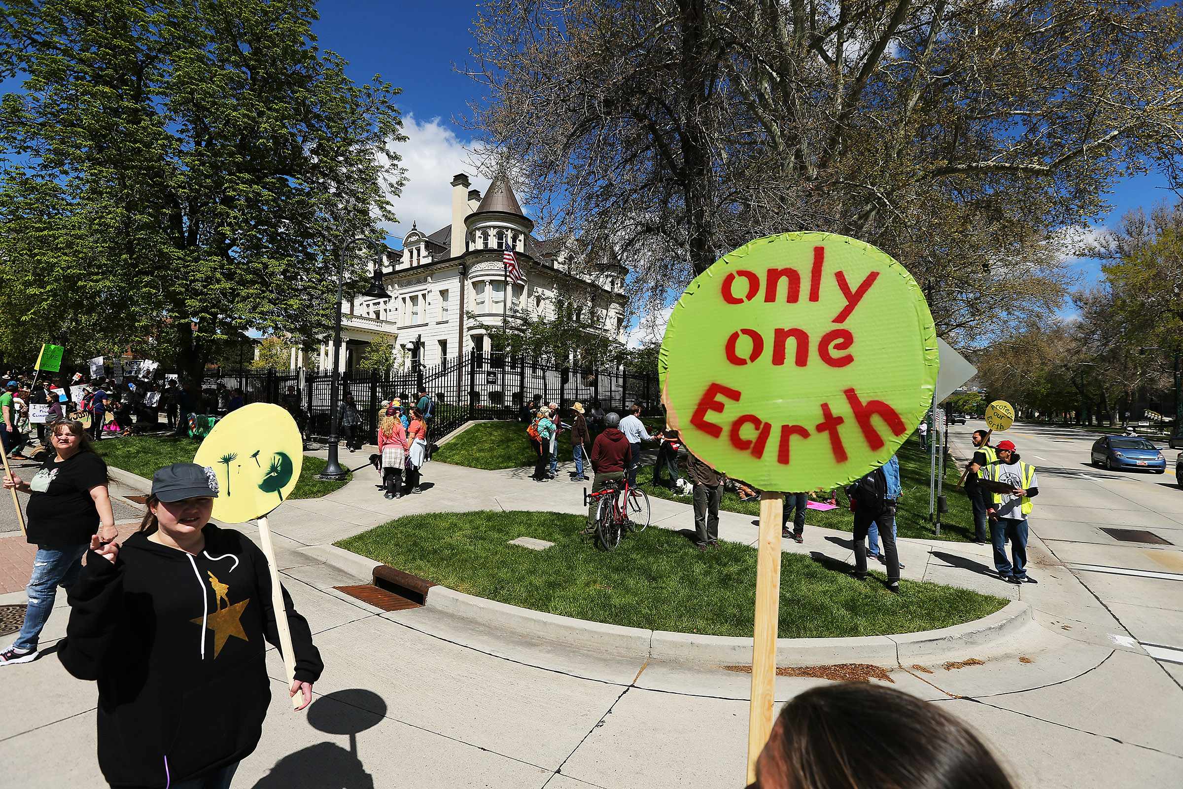 People hold up signs while marching to the Governor's Mansion during the Utah People's Climate March in Salt Lake City in 2017.