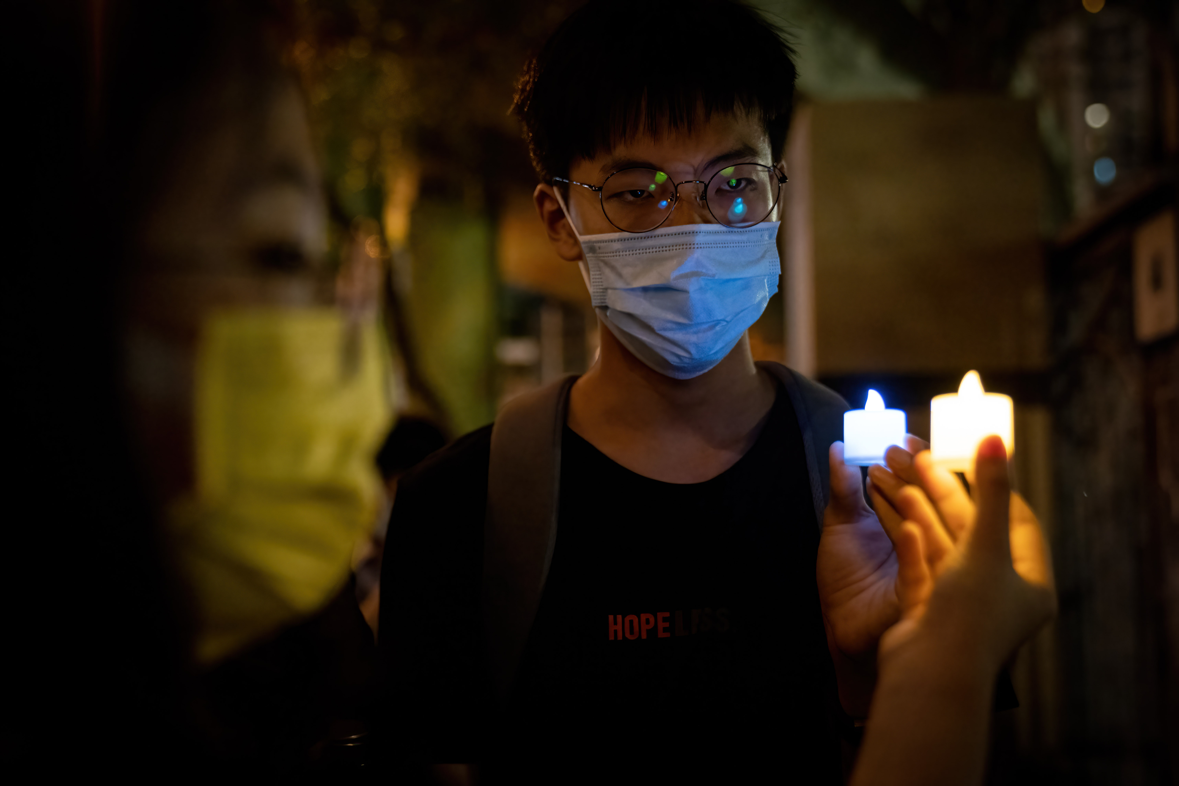 A man holds a burning candle as part of the small protests by Hong Kong people during the Tiananmen Square anniversary.