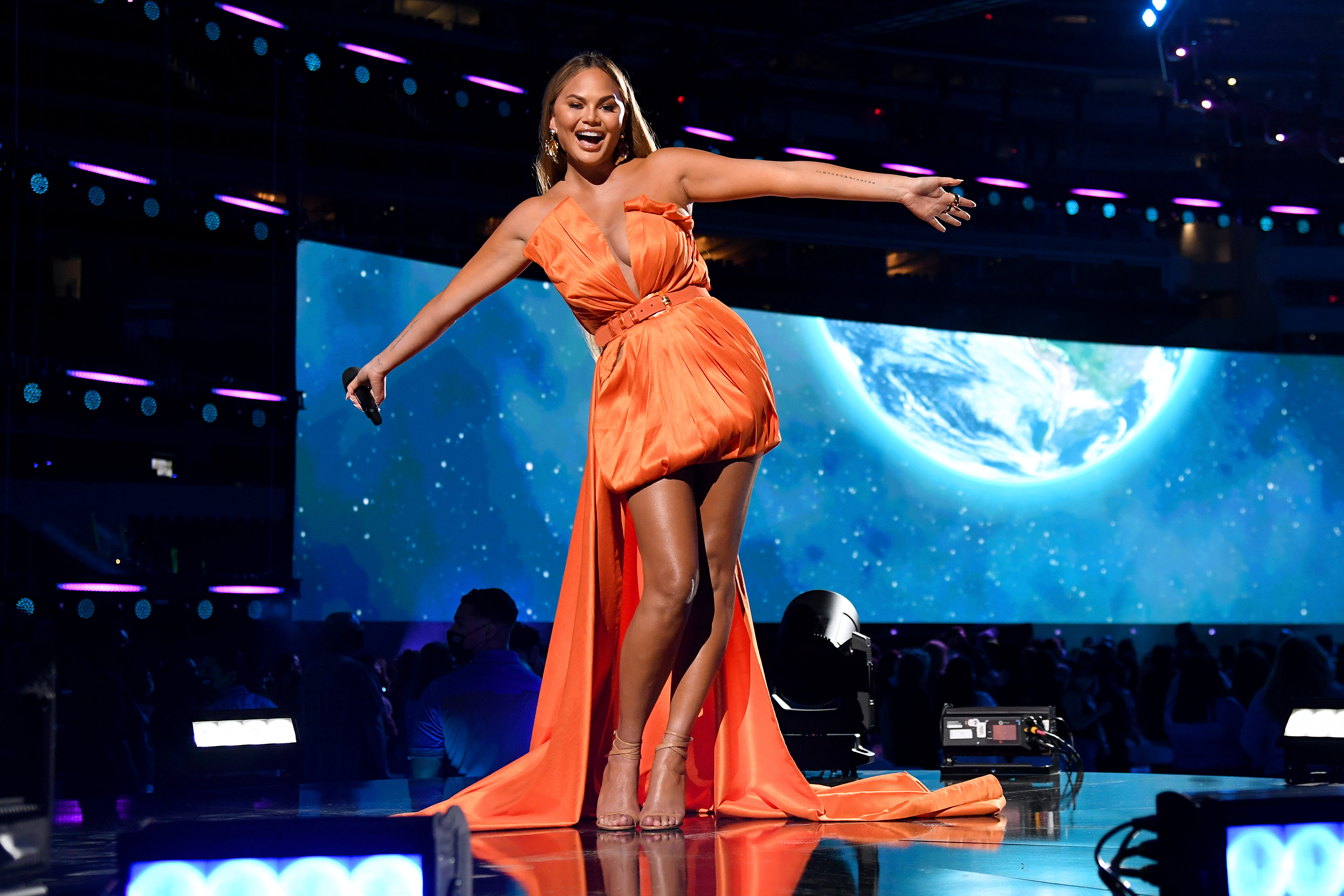 Chrissy Teigen onstage holding her arms out wide.