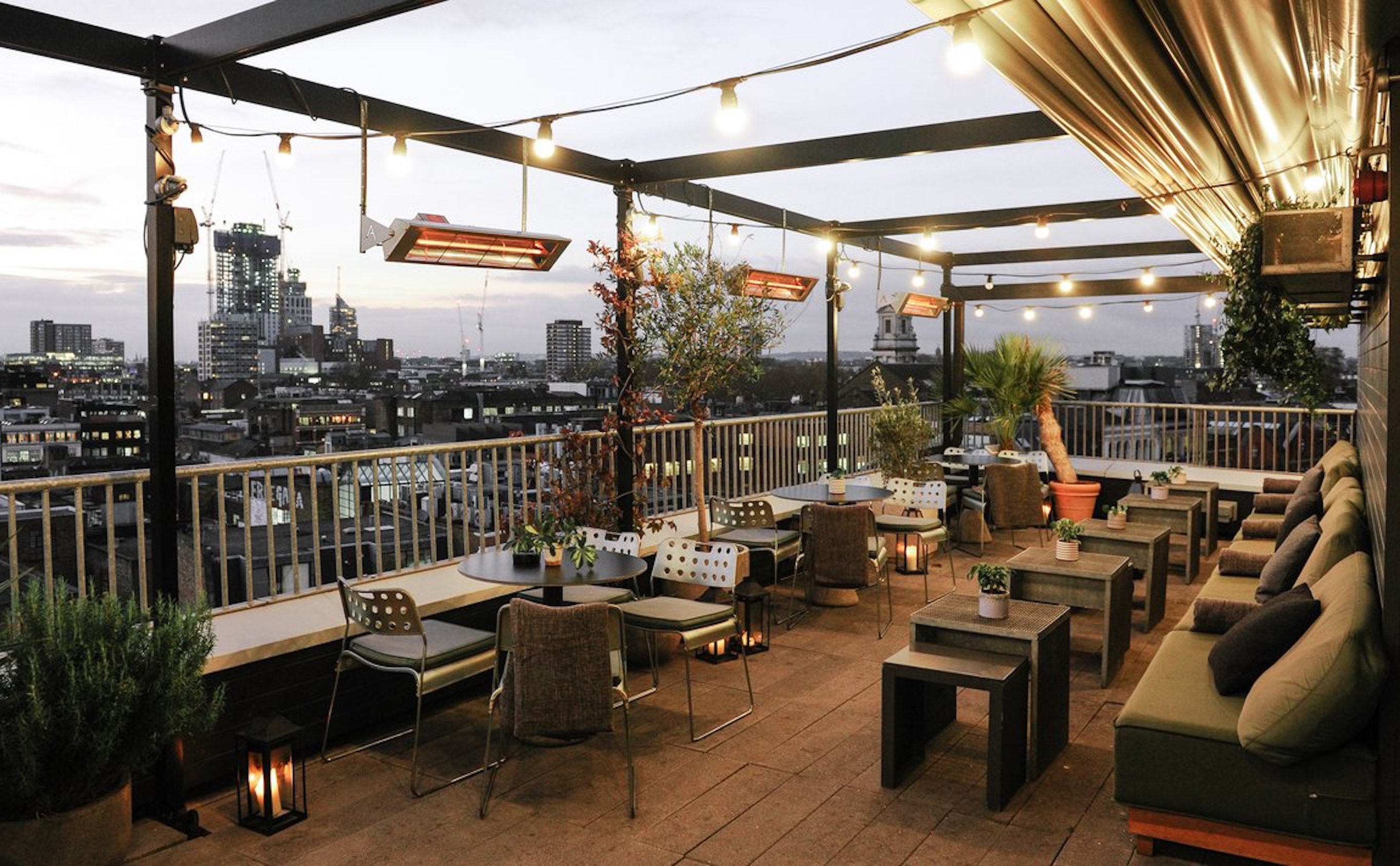 A hotel rooftop in Shoreditch adorned with filament bulbs, cushioned seating, and wooden decking