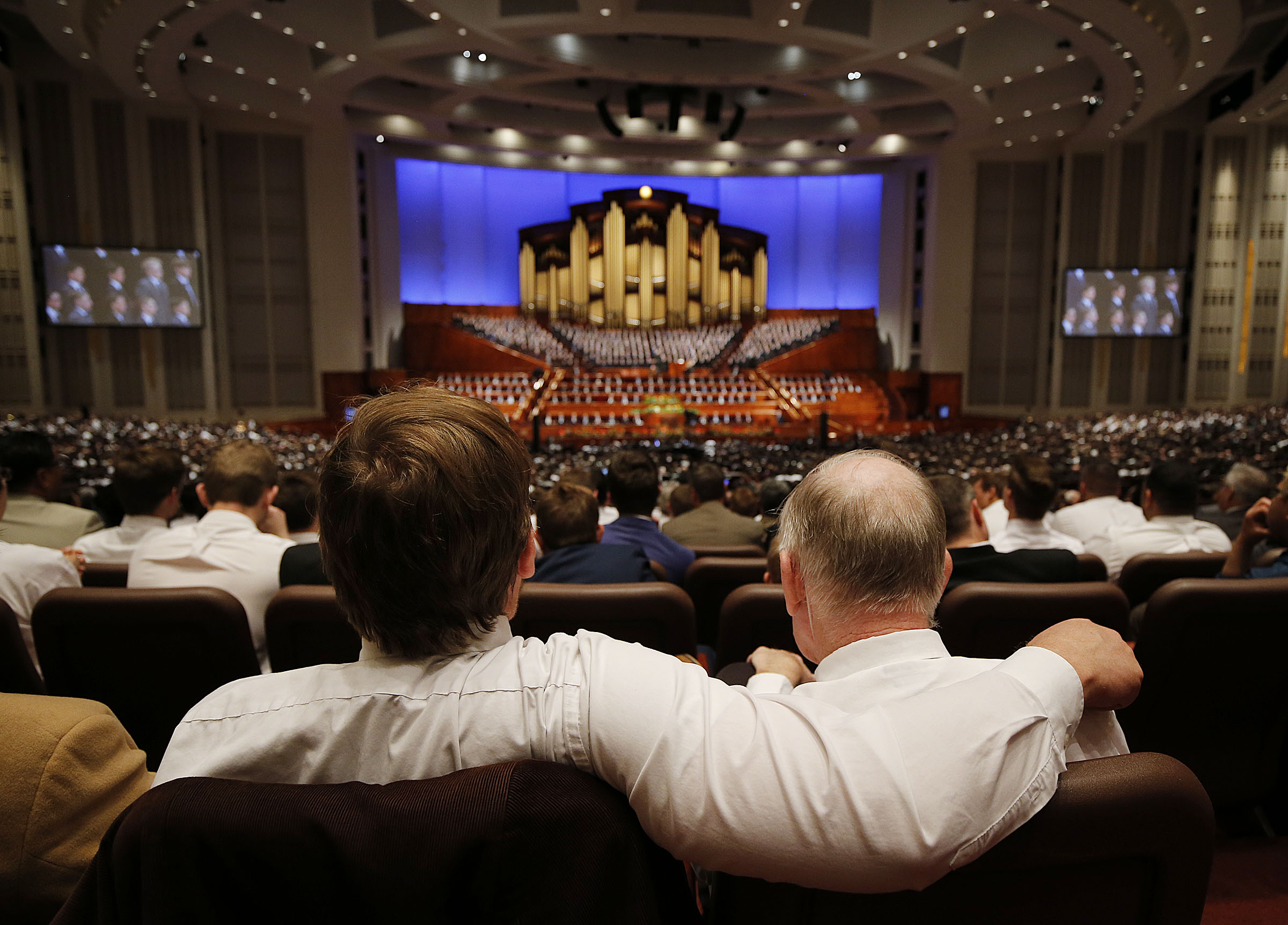 Johnny Walker, left, sits with his father, Andy, during the priesthood session of the 189th Annual General Conference in the Conference Center.
