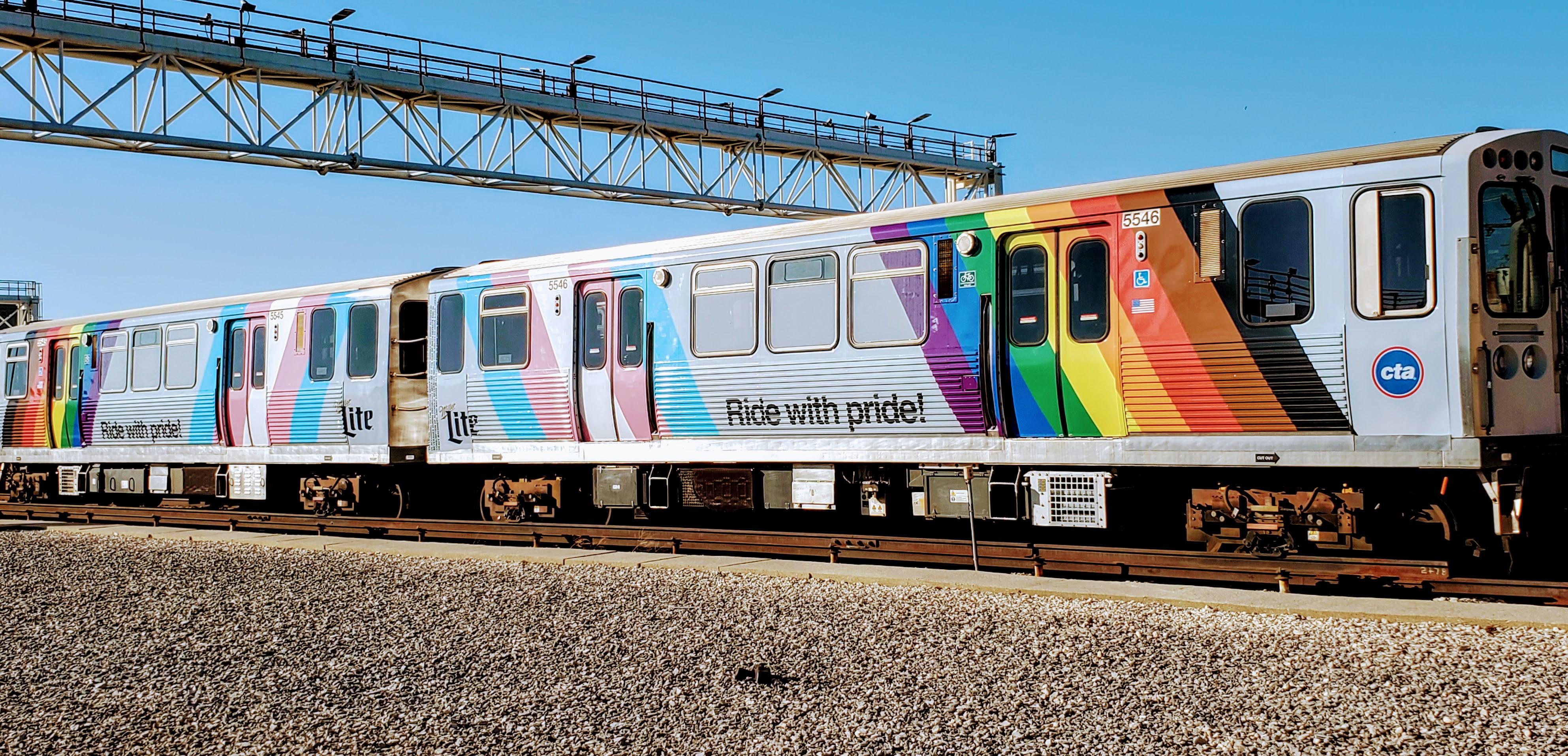 The Pride Train rides through a rail station.