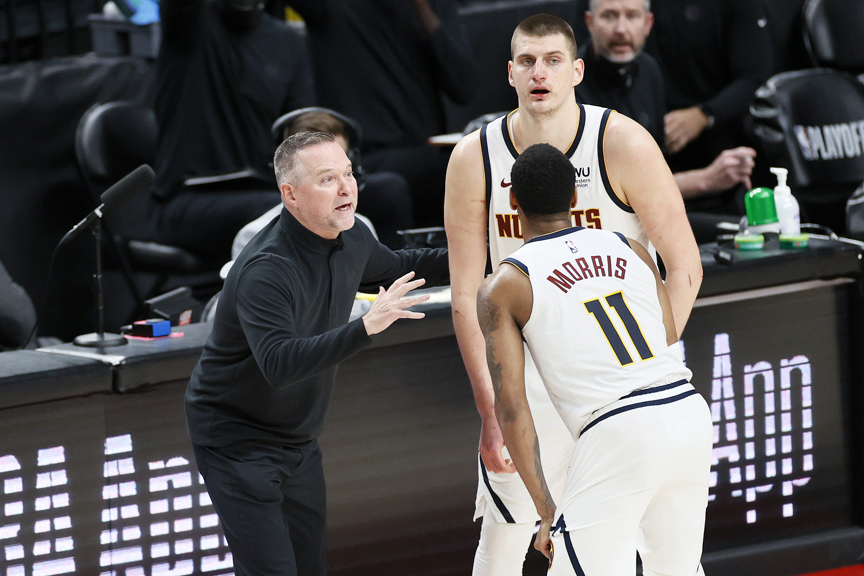 Head coach Michael Malone of the Denver Nuggets talks with Nikola Jokic and Monte Morris in the fourth quarter against the Portland Trail Blazers during Round 1, Game 6 of the 2021 NBA Playoffs at Moda Center on June 03, 2021 in Portland, Oregon.