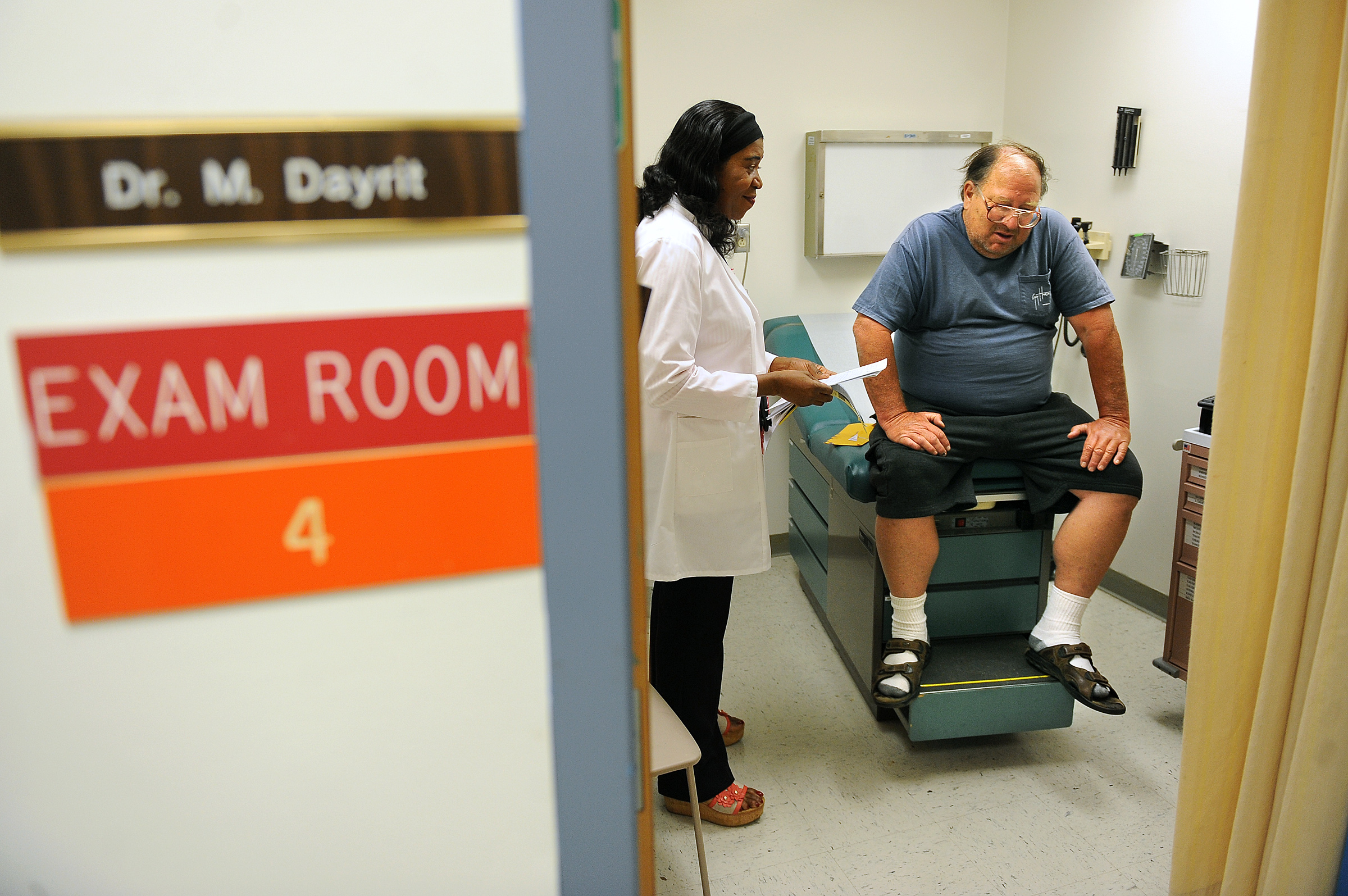 """A patient sits on a doctor's exam table while the doctor stands beside them. Visible outside the room are signs reading, """"Dr. M. Dayrit, exam room 4."""""""