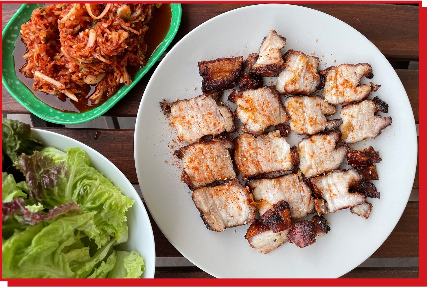 Pork belly sliced and on a plate with red seasoning on top. Lettuce and kimchi are on separate plates nearby.